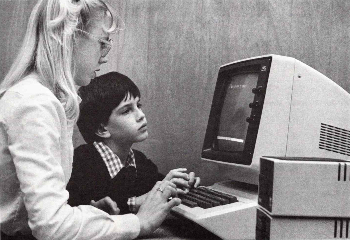 a black and white photo from 1983 shows a male elementary school student sitting at a computer with a female teacher who is using the keyboard