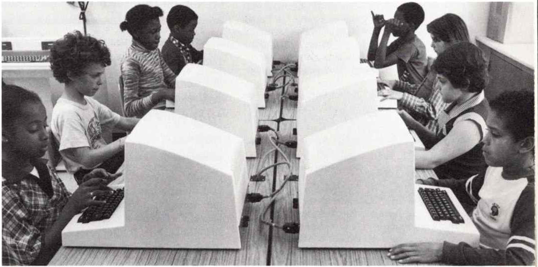 a black and white photo from 1983 shows eight elementary school students male and female facing each other as they sit and work at two rows of computers