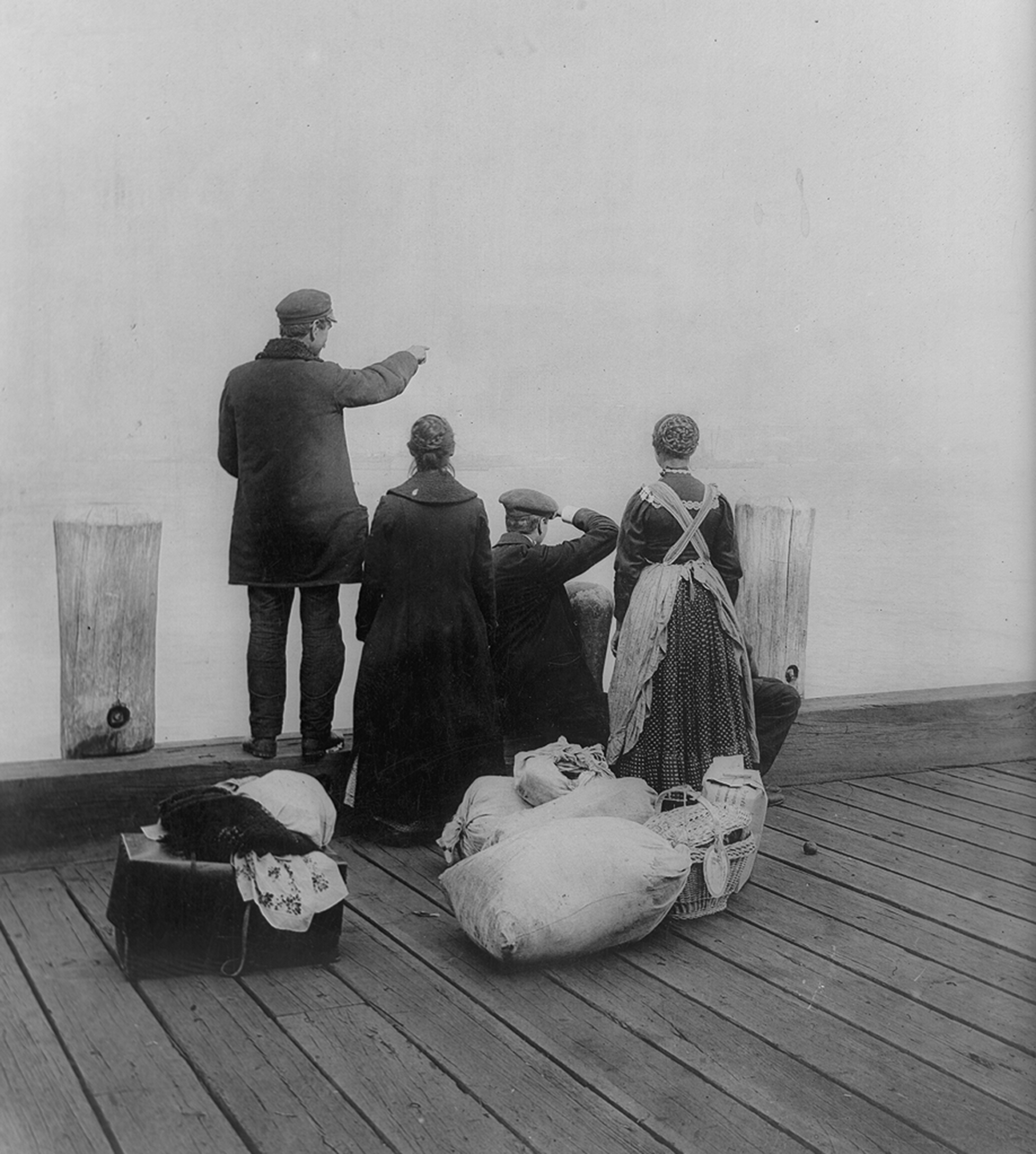 a black and white photo from 1912 of four immigrants and their belongings, seen from behind, on a dock, looking out over the water
