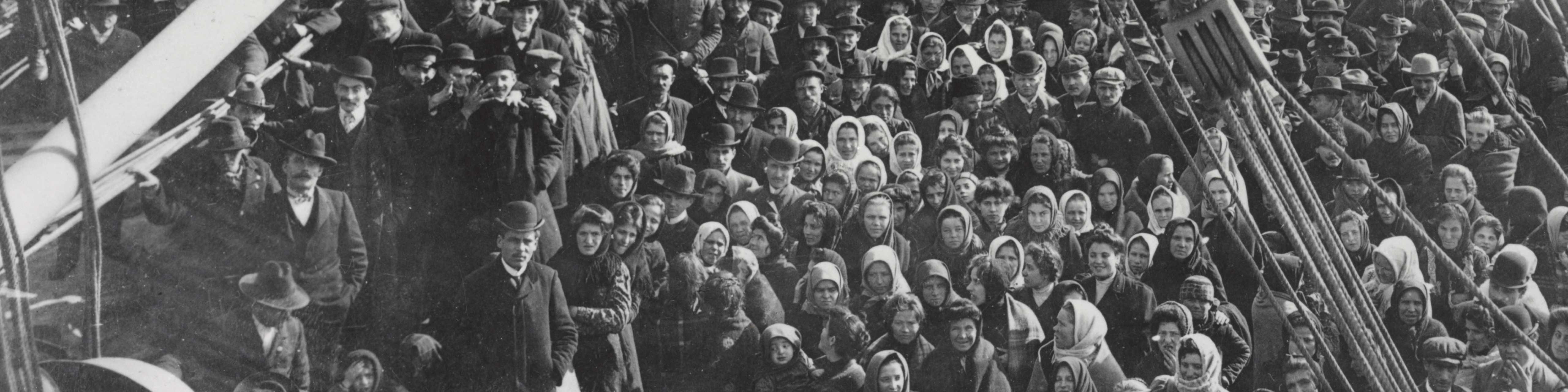 A black and white photograph from 1906 showing a crowd of men and women immigrants on deck of the S.S. Patricia facing camera