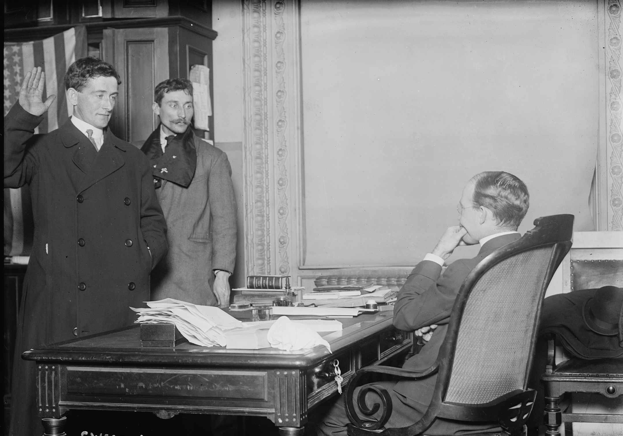 a black and white photo showing a judge in chambers swearing in a new citizen