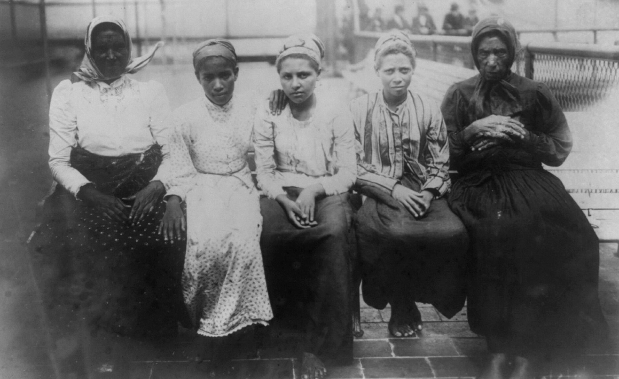 a black and white photograph from 1910 photograph showing five female immigrants sitting on dock at Ellis Island
