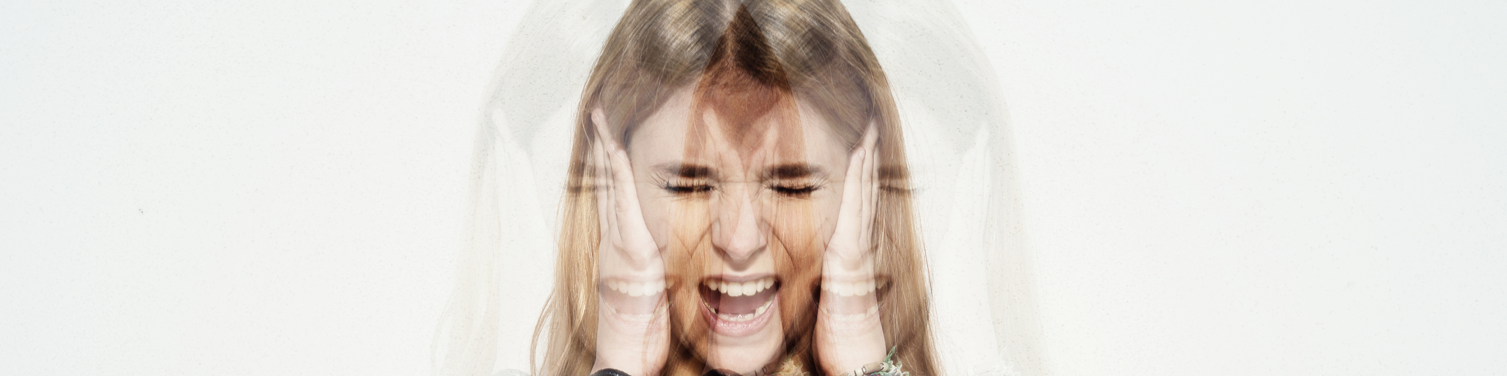 a photo of a young woman holding her head and screaming in confusion