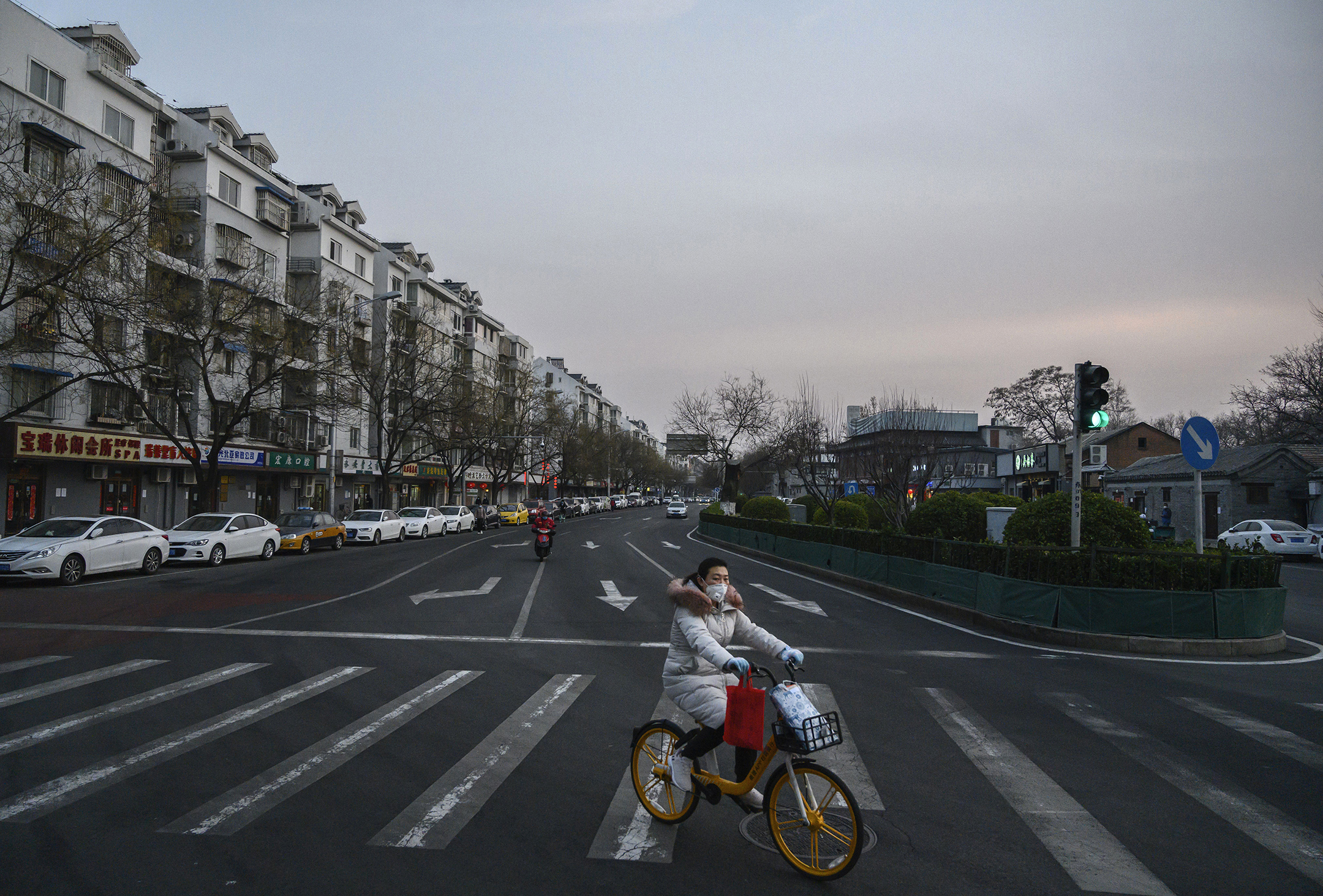 A Chinese woman wears a protective mask as she rides a bike in a nearly empty street in Beijing, China