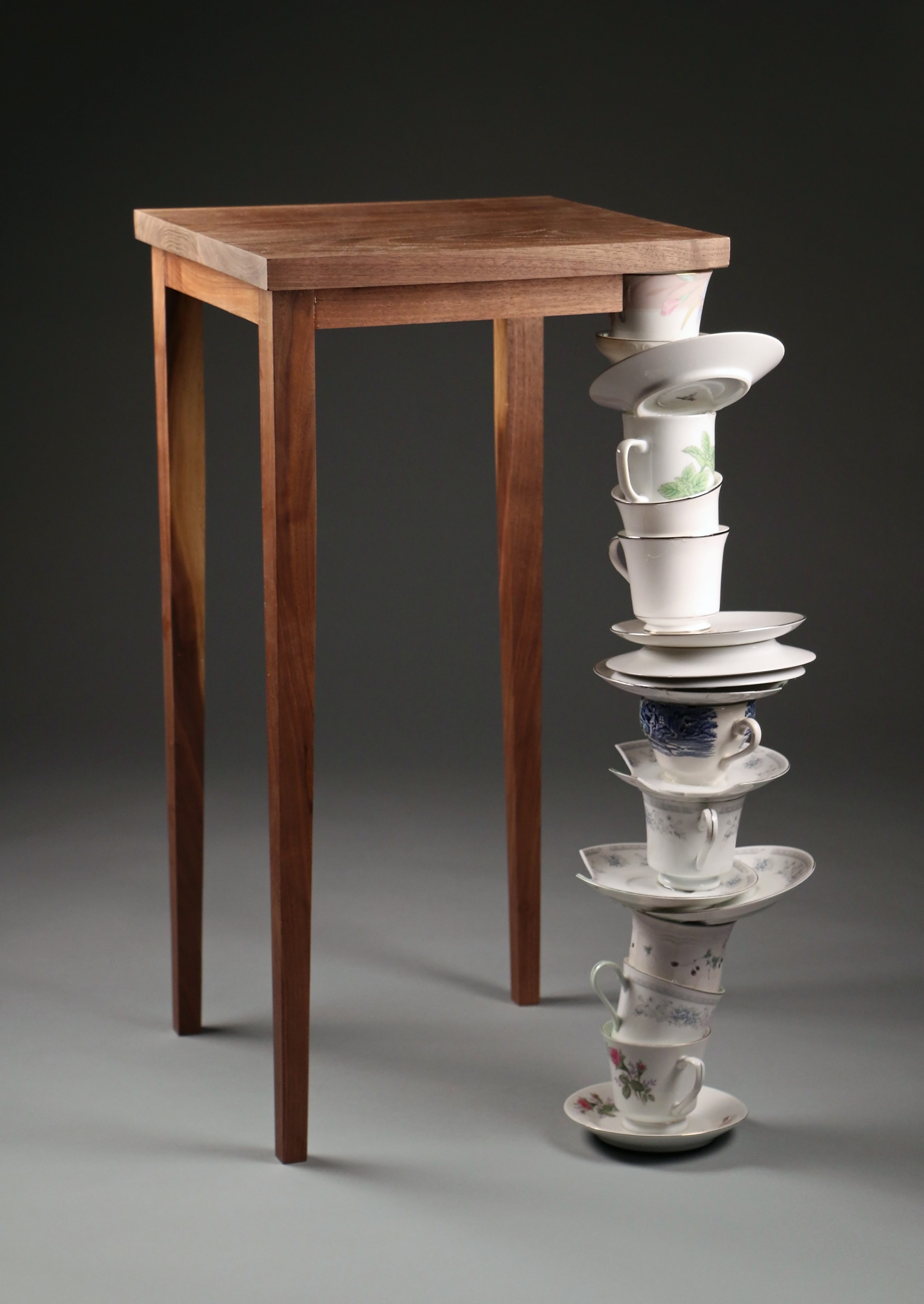 3D art of a table with one leg replaced by a stack of cups and saucers