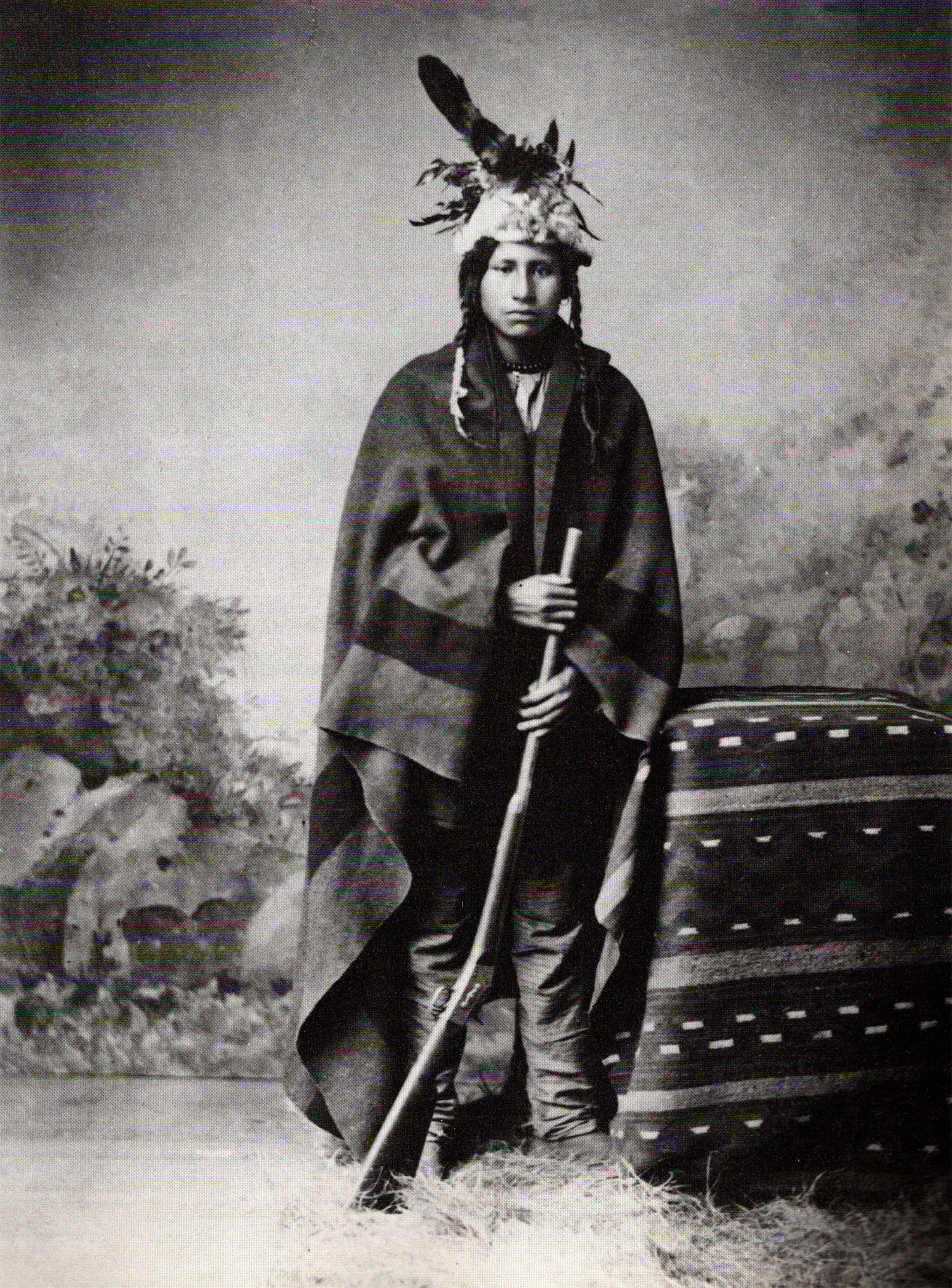 a posed black and white photo of a Native American wearing a headdress and holding a rifle