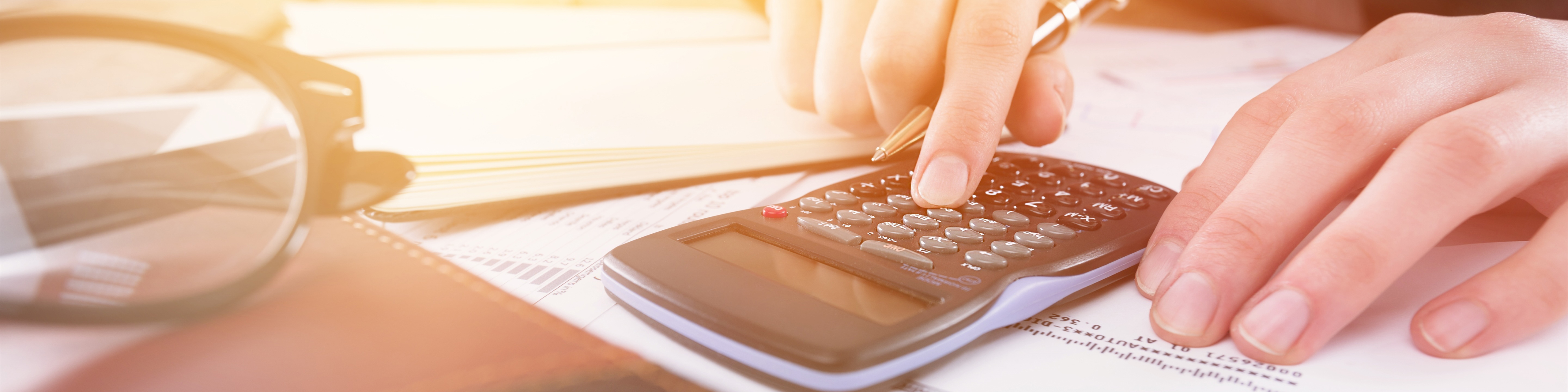 pair of hands using a calculator, which is sitting atop a pile of paperwork