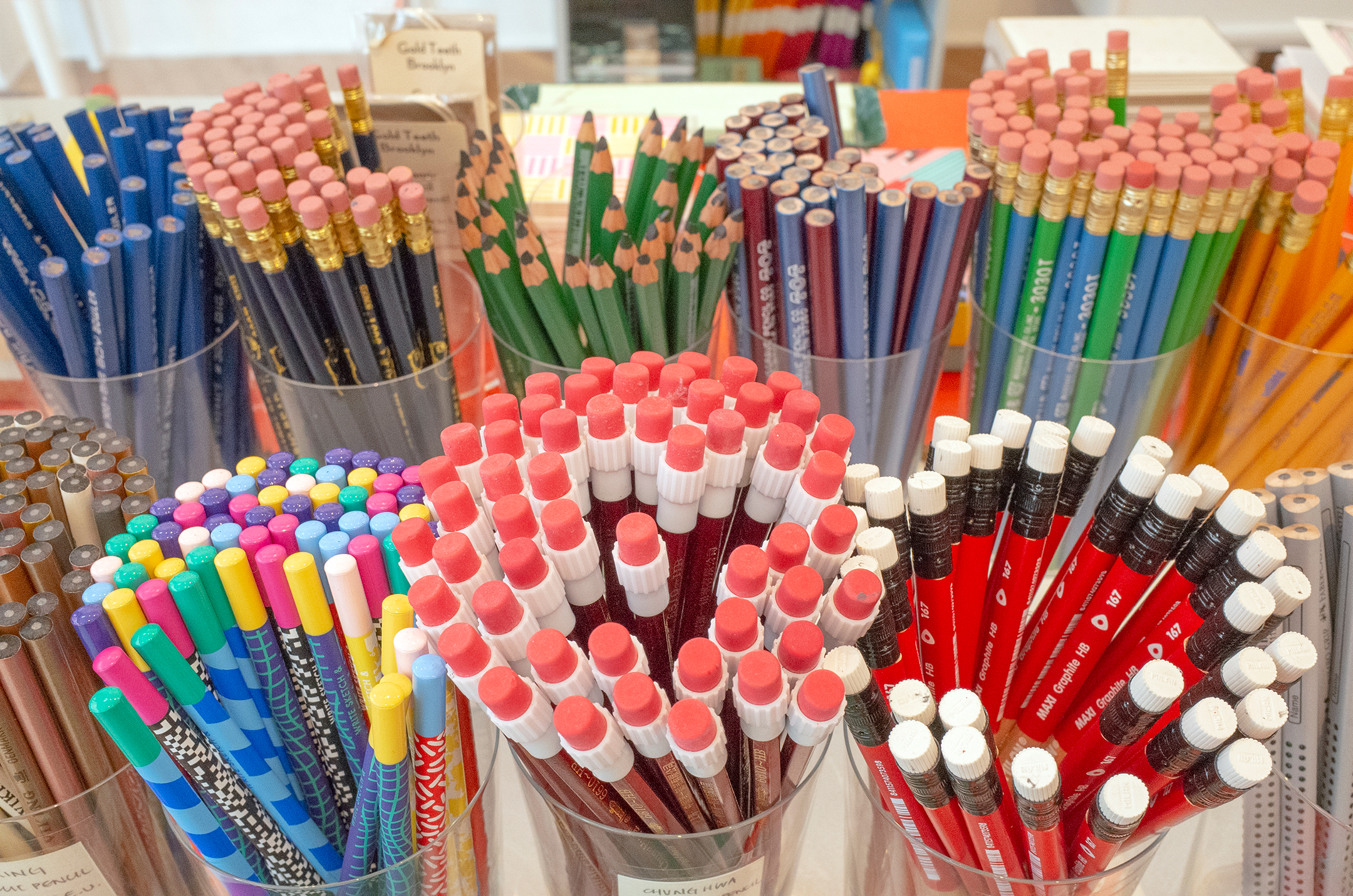 a photograph of ten different types of pencil, organized in cups with their eraser ends facing up