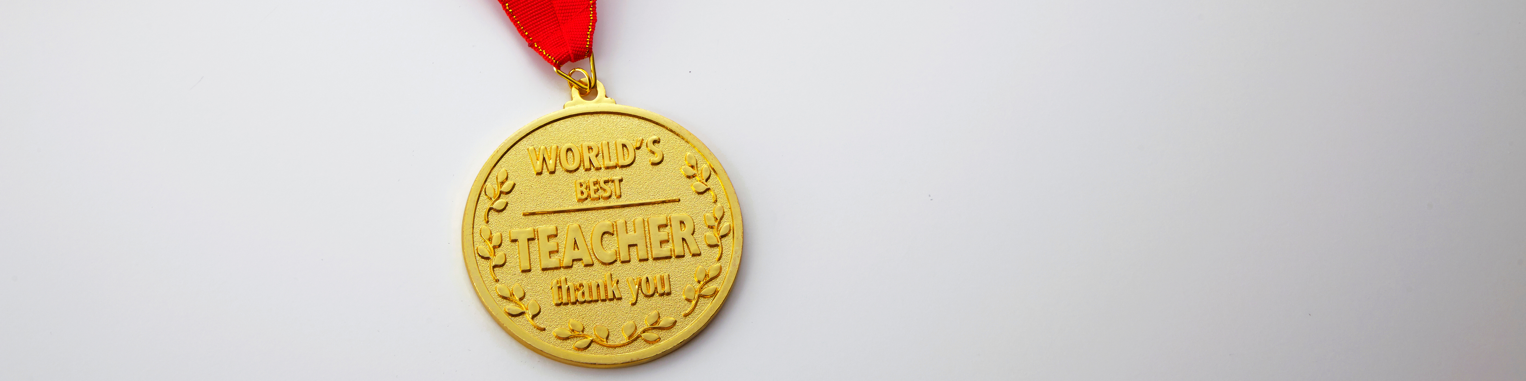 a gold medal at the end of a red ribbon on a white background