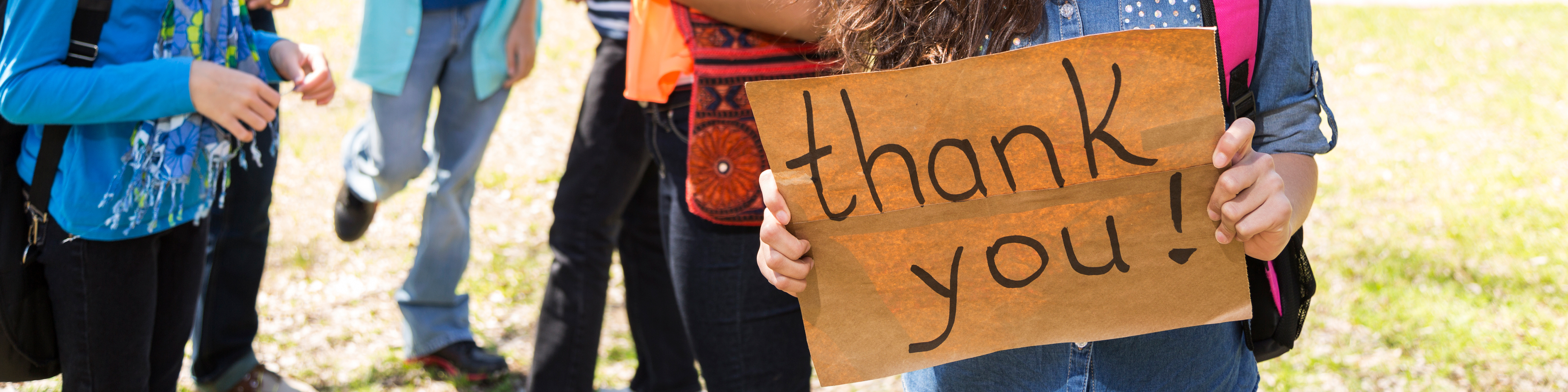 a handwritten sign that reads thank you being held by a young woman