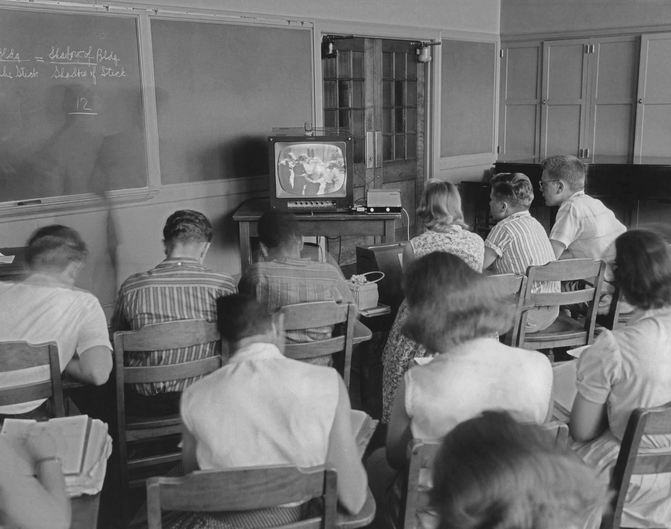 black and white photo of a classroom of students watching a lesson on a television