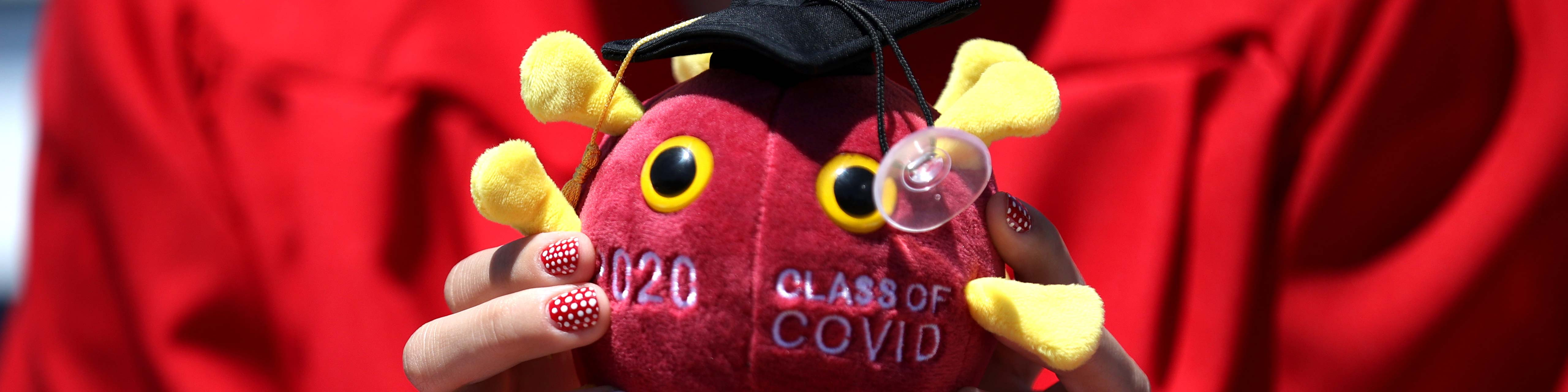 a graduating senior holds a stuffed representation of the covid-19 virus