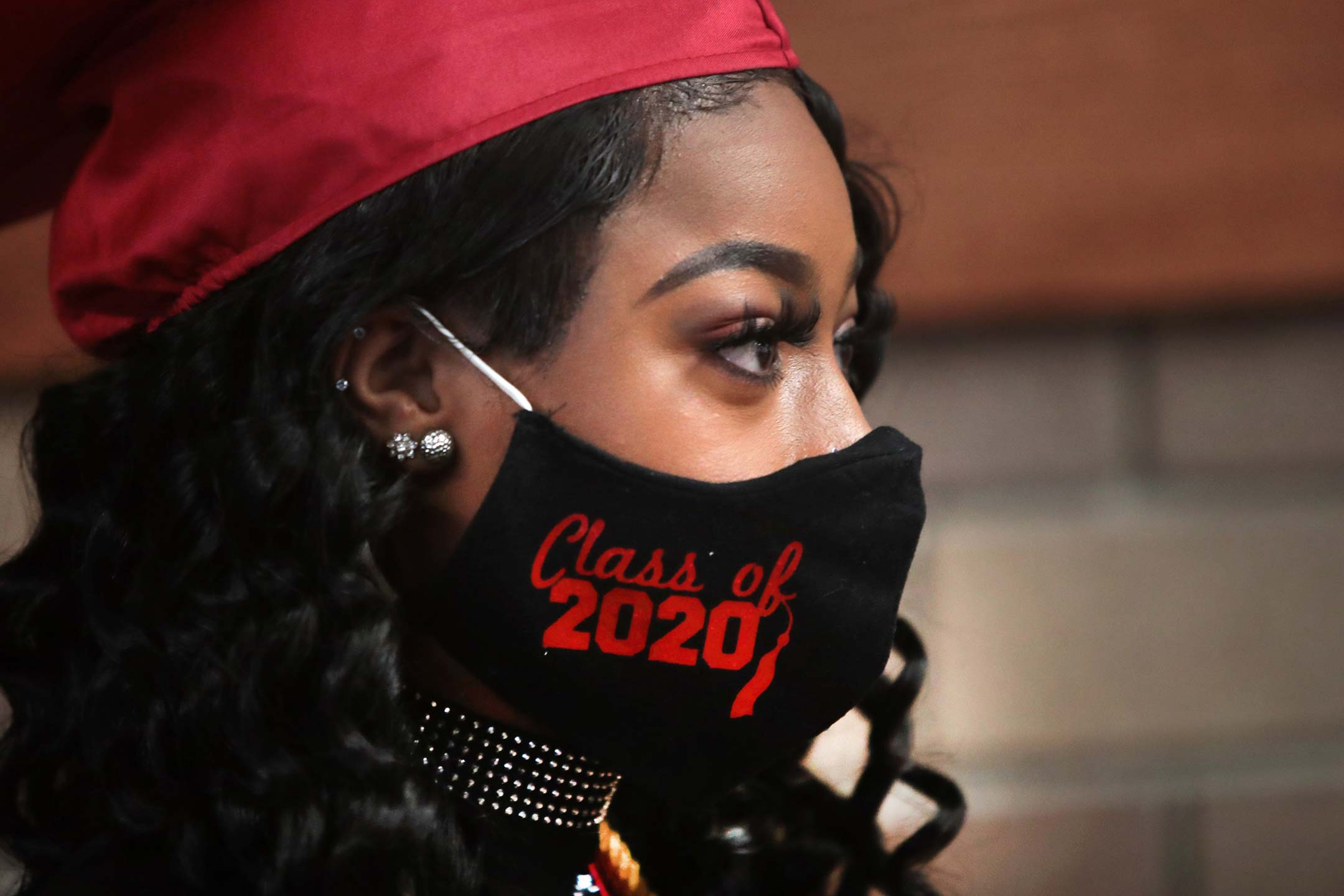 a young black woman, shown in profile, wears red graduation regalia and a black face mask with class of 2020 written on it