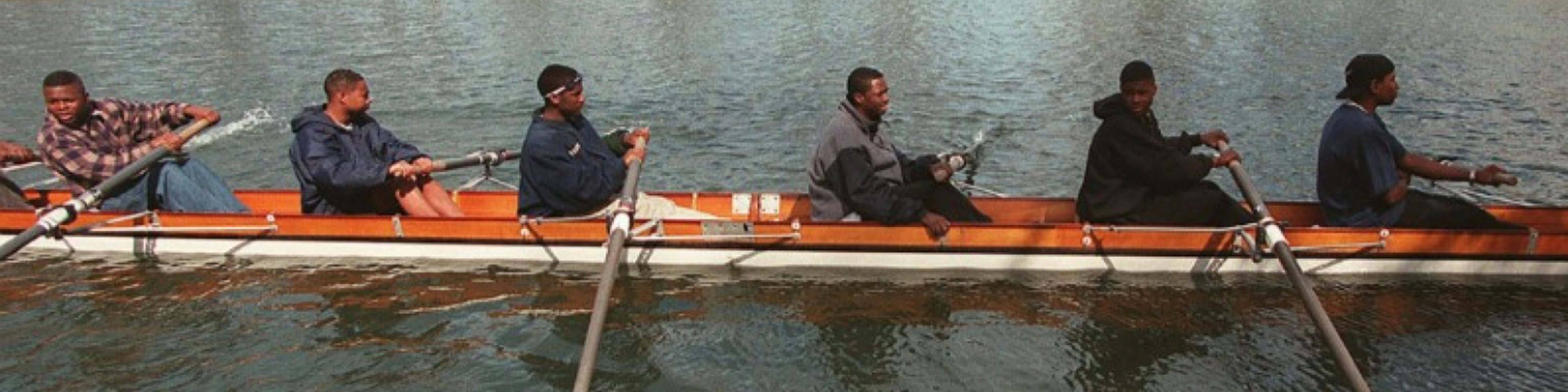 a team of young black men rowing crew
