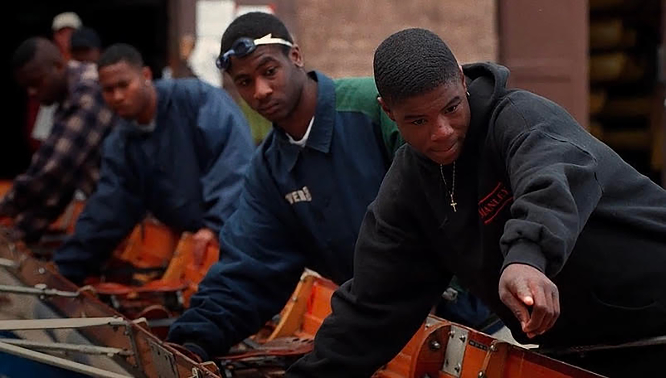 A group of young black men work on a boat for their crew team