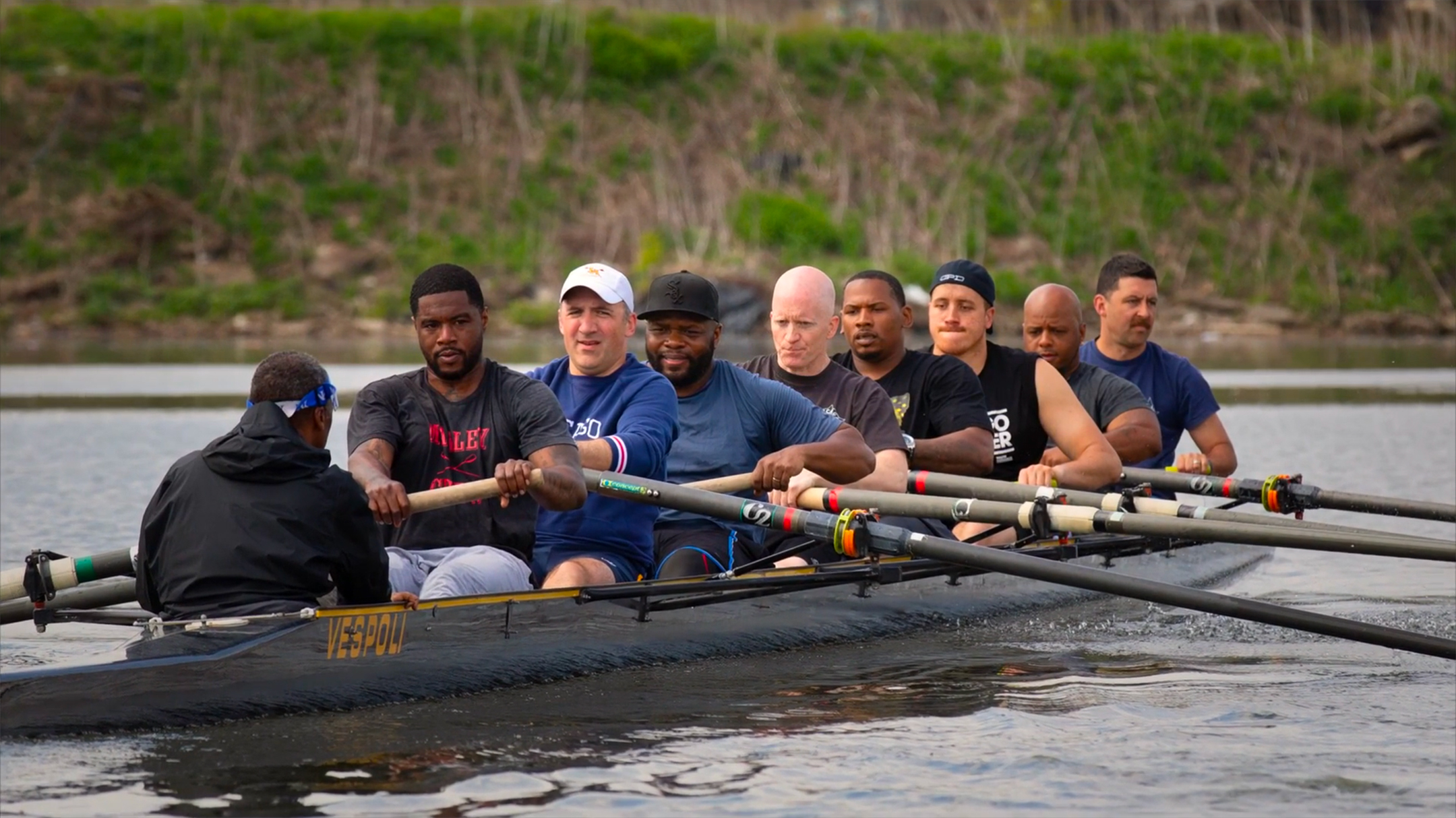 nine people in a boat, five black and four white, rowing on a river