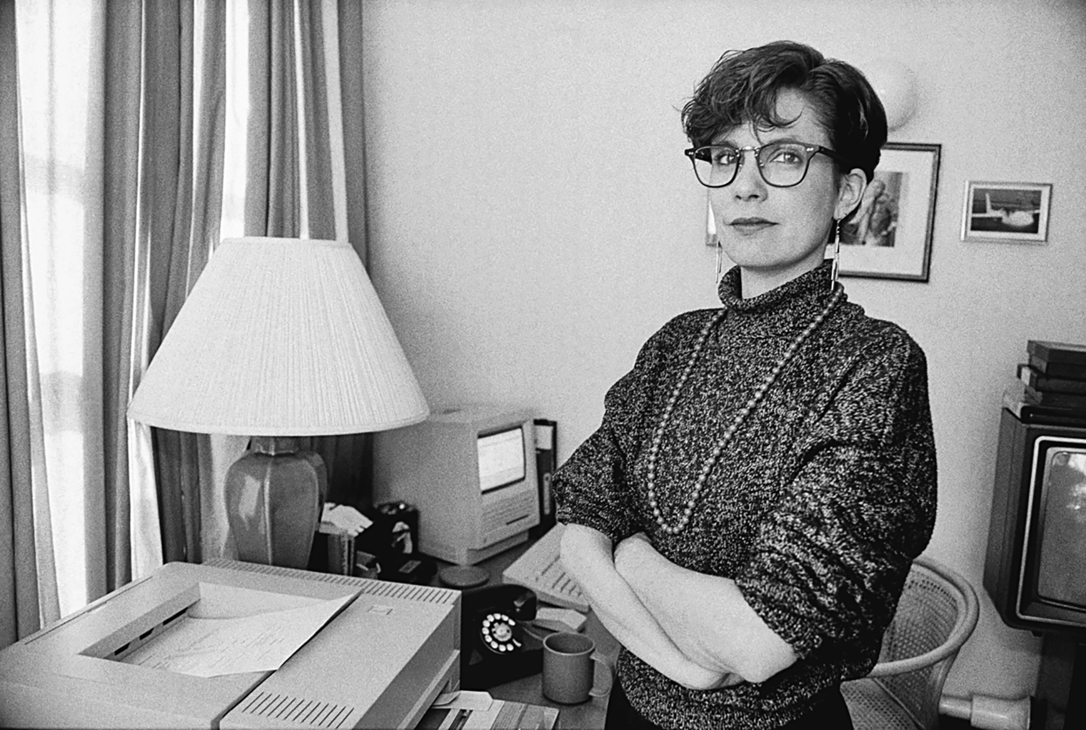black and white photo of a woman with short hair and glasses standing with her arms crossed in front of a computer and printer