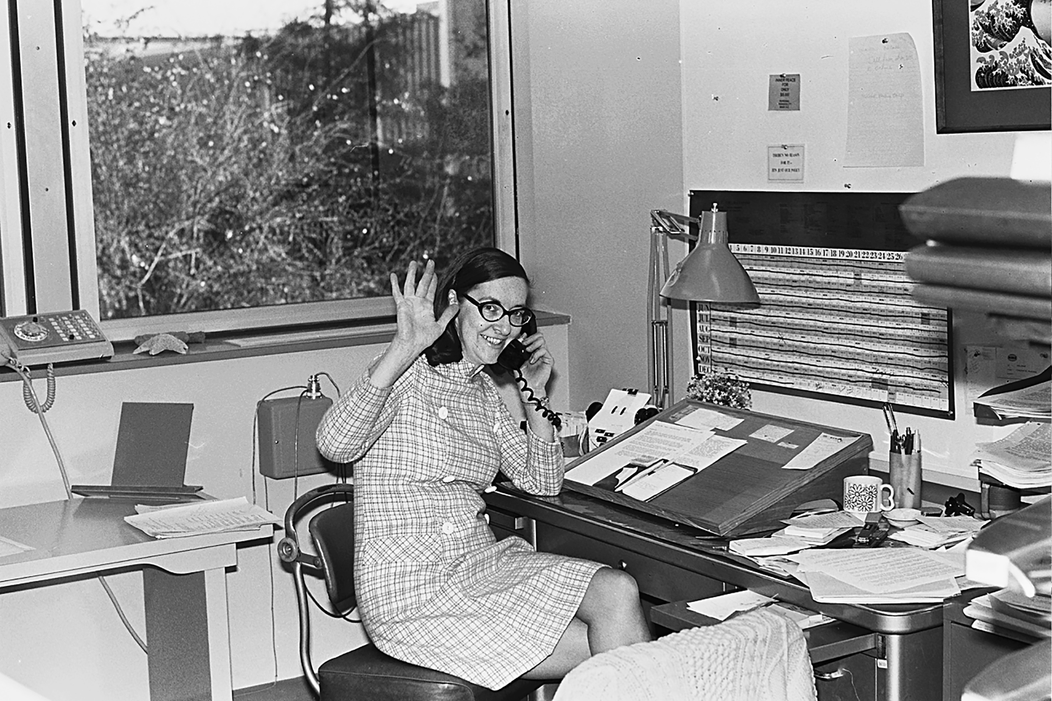 black and white photo of a woman in glasses sitting in front of a computer and talking on the phone while smiling and waving