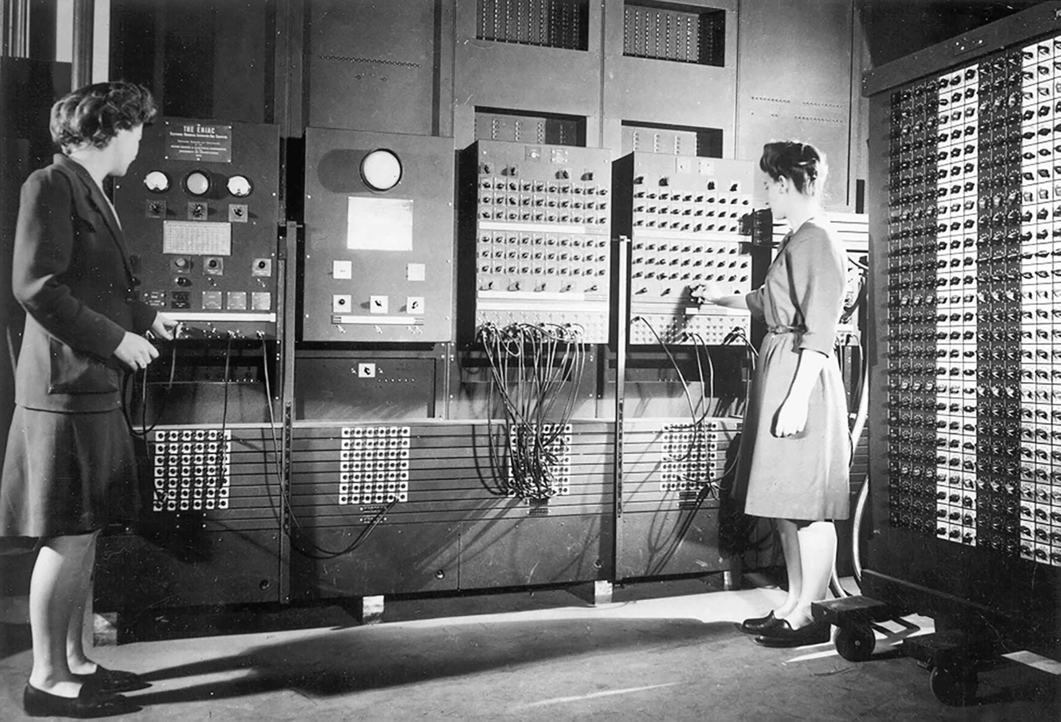 Black and white photograph of two women in the 1940s working on the world's first computer