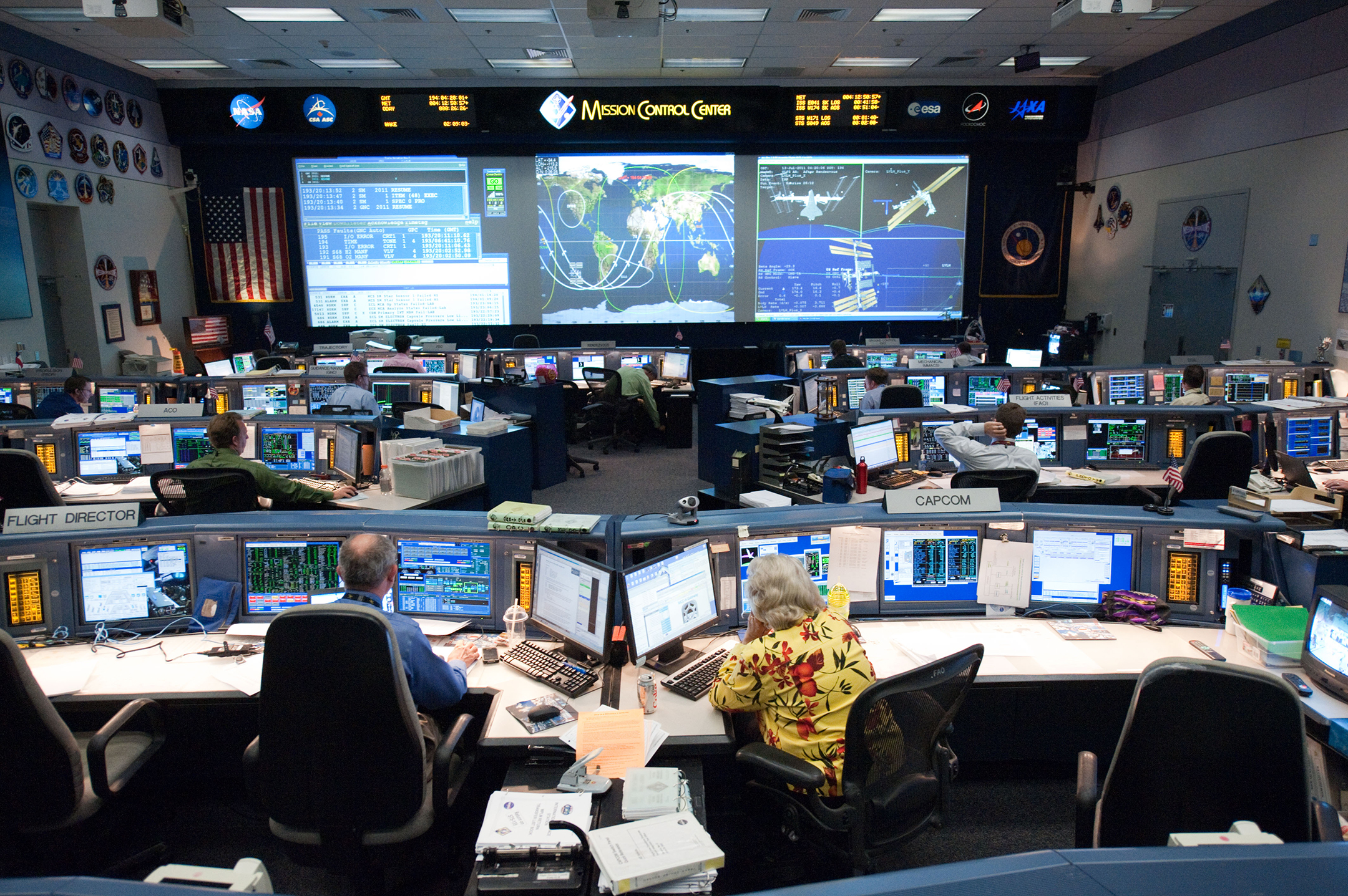 wide angle shot of nasa's mission control center, showing people sitting at computer terminals