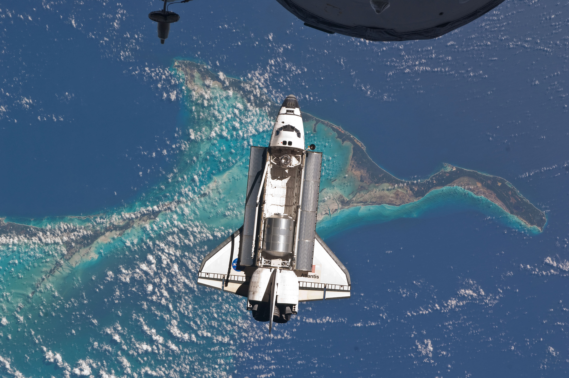 photo of space shuttle in orbit around the earth with its payload bay doors open