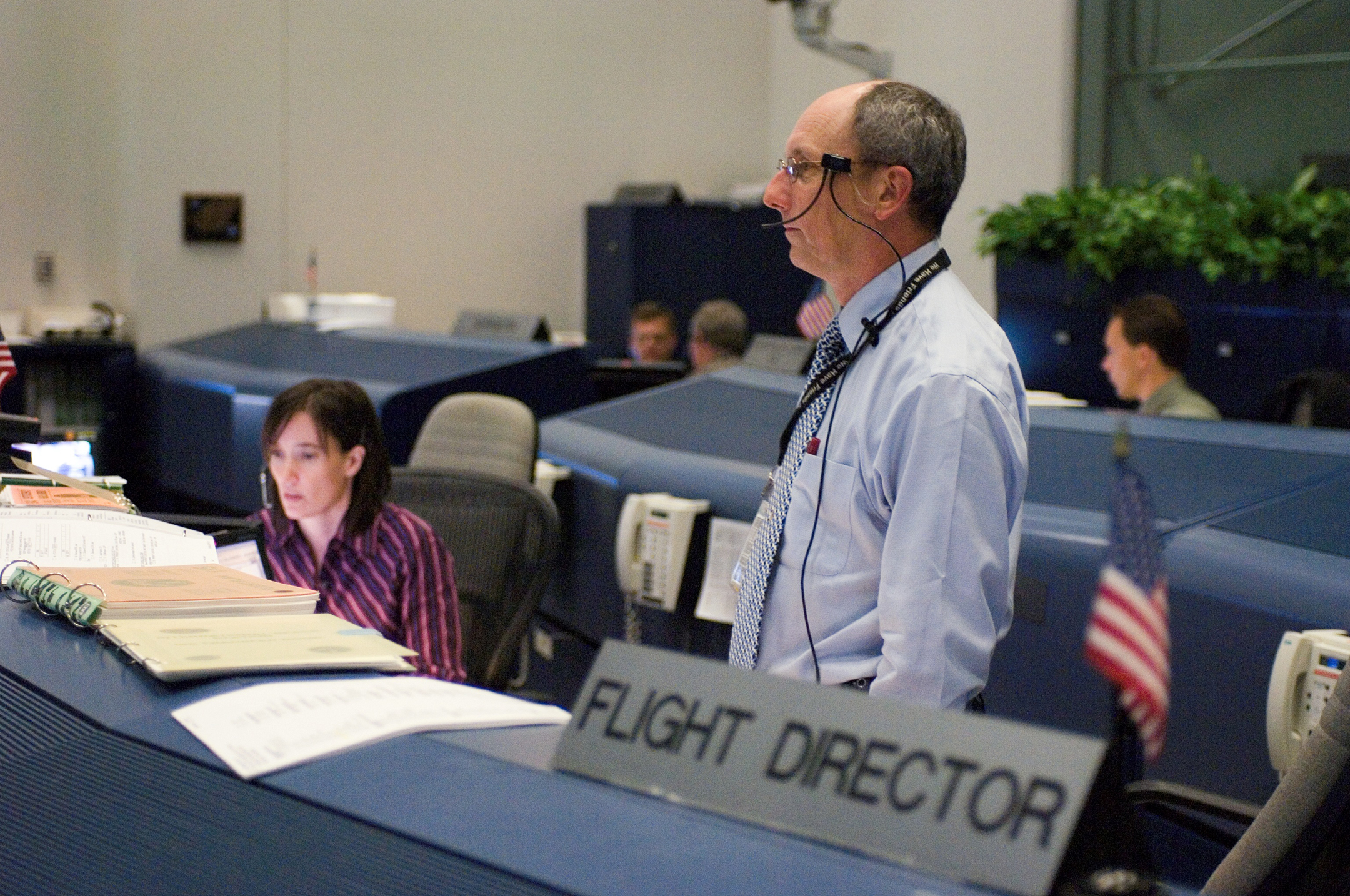 paul dye wears his headset and stands in mission control during a shuttle mission