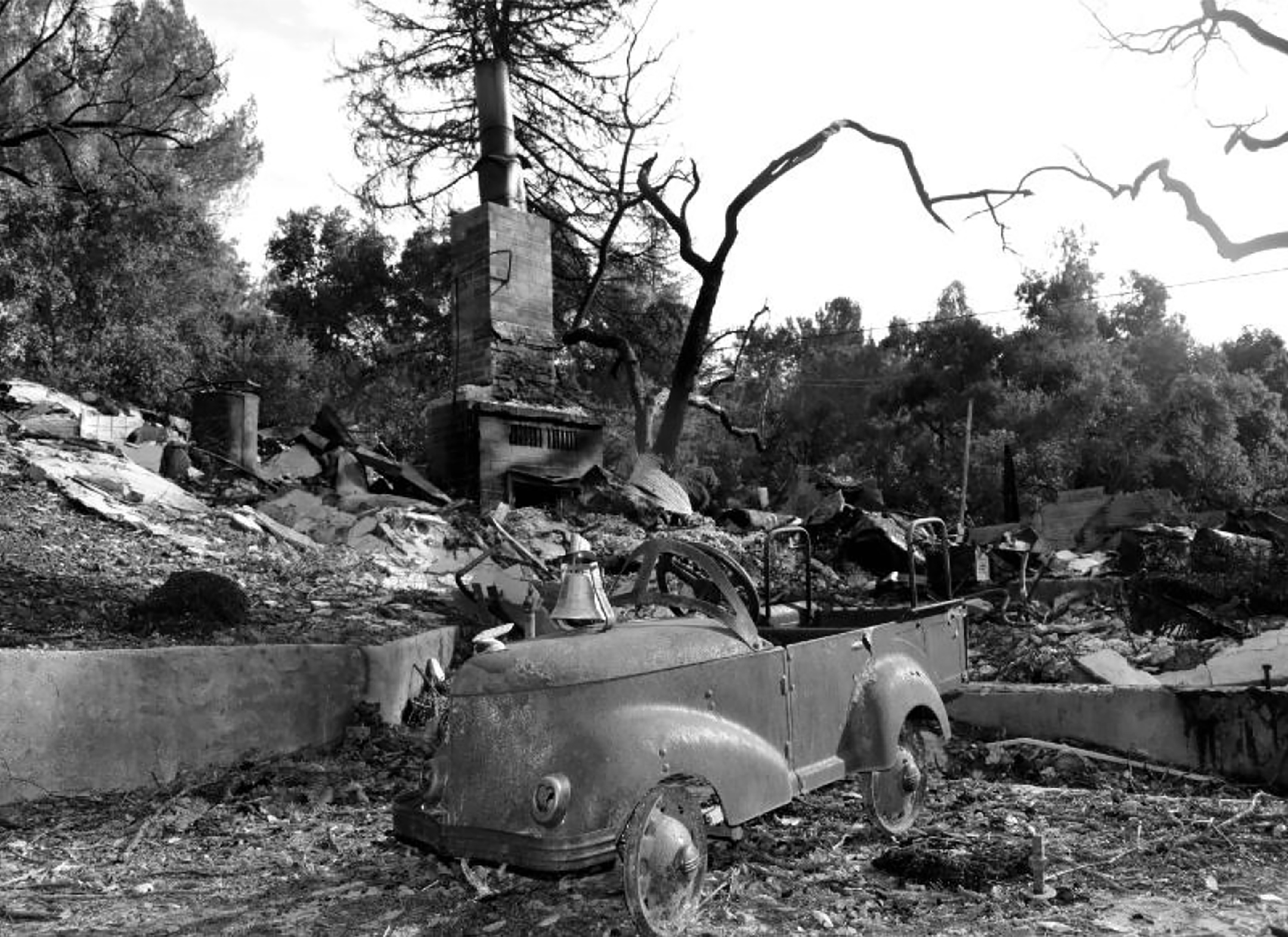 black and white photograph of a burned house and landscape with a damaged child-size car in the center of the frame