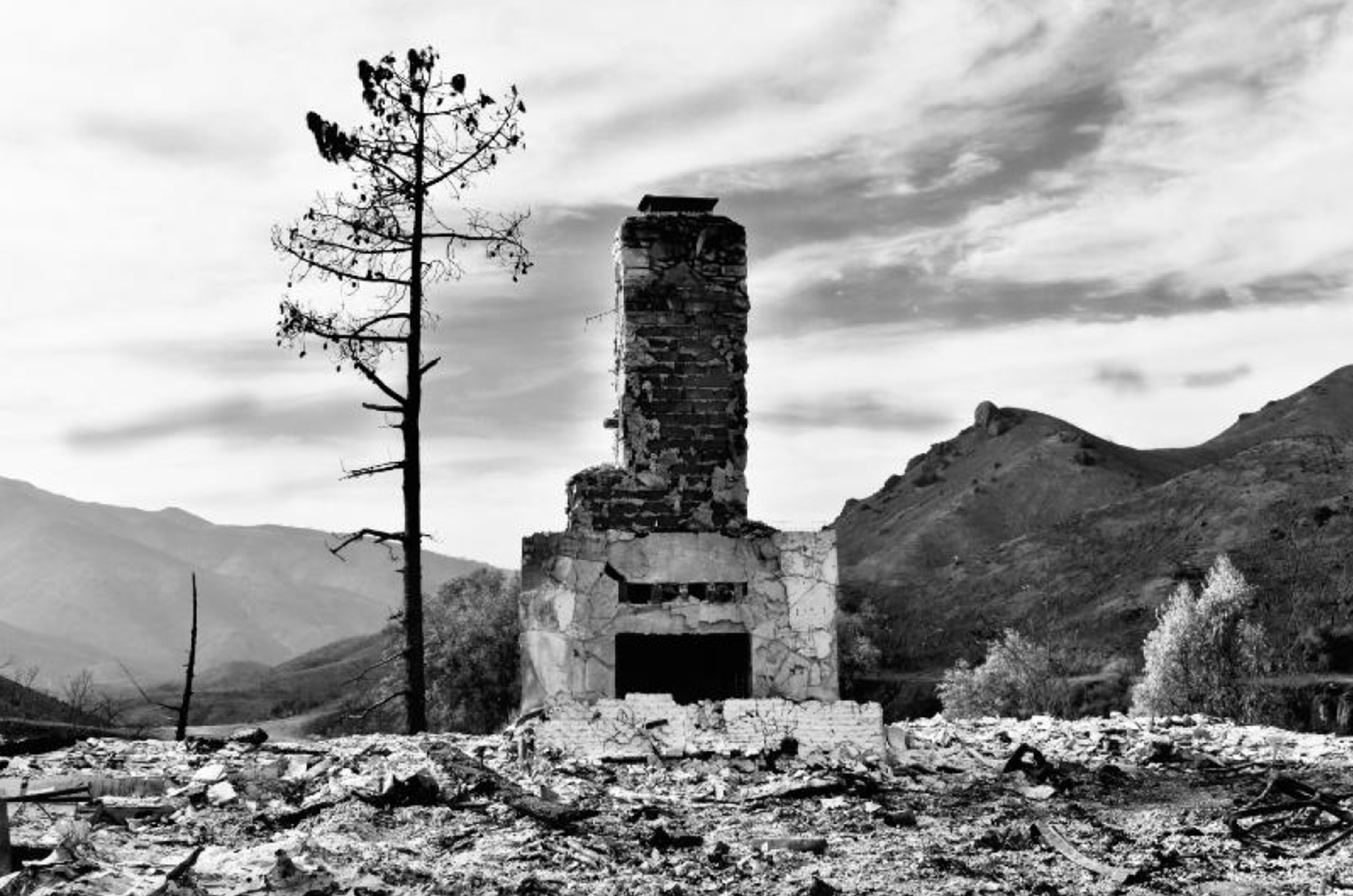 black and white photograph of a burned landscape with the charred remains of a house — a fire place and chimney — at the center of the frame
