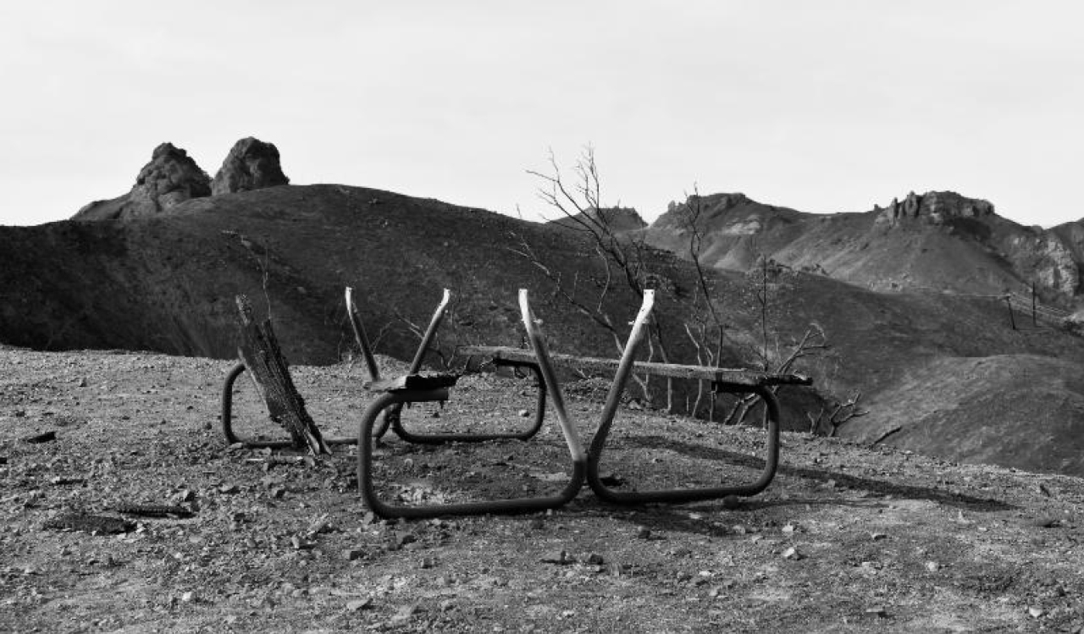 black and white photograph of a burned landscape with the charred remains of a house — the frame of a table — at the center of the frame