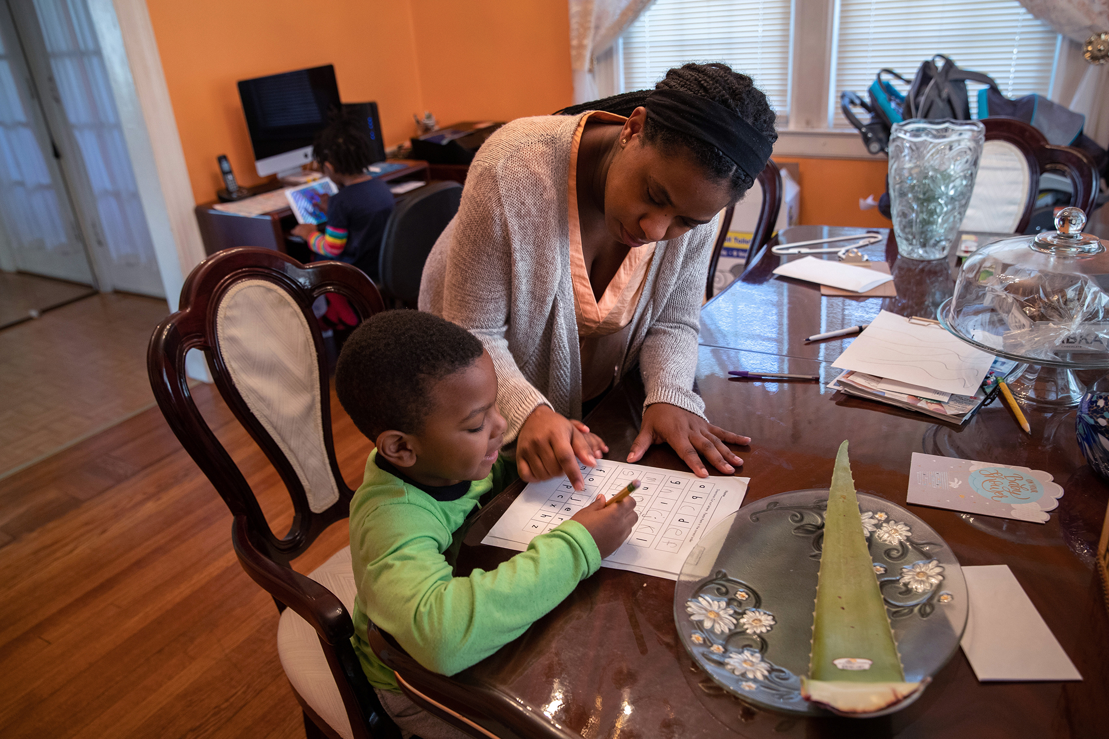 a mother stands with her son, who is seated and doing homework, and points at his school worksheet