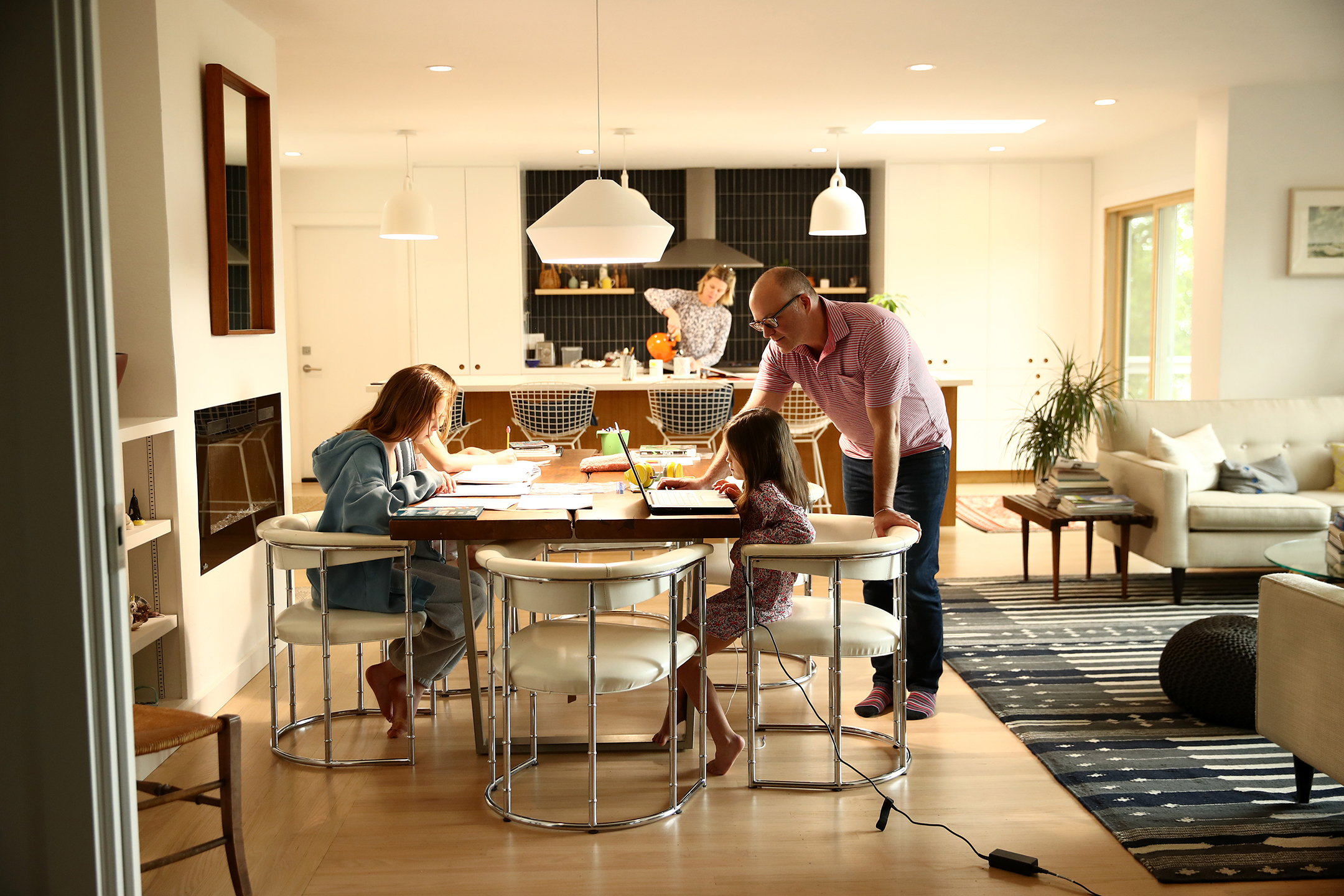 a father stands while he helps his three daughters, sitting at a large table, with their homework