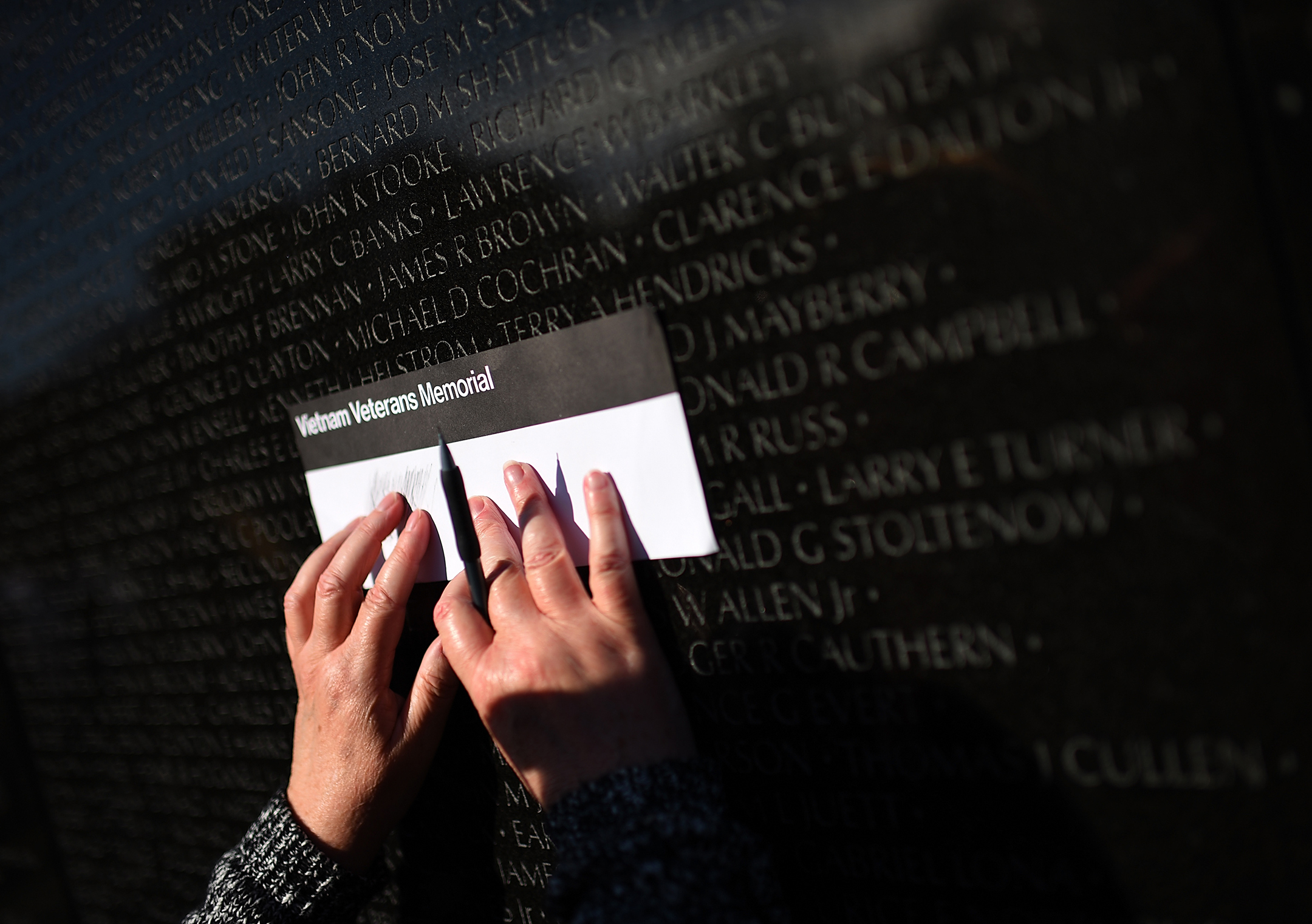 two hands hold a piece of paper up to the vietnam veterans memorial to make an etching of a name on the wall
