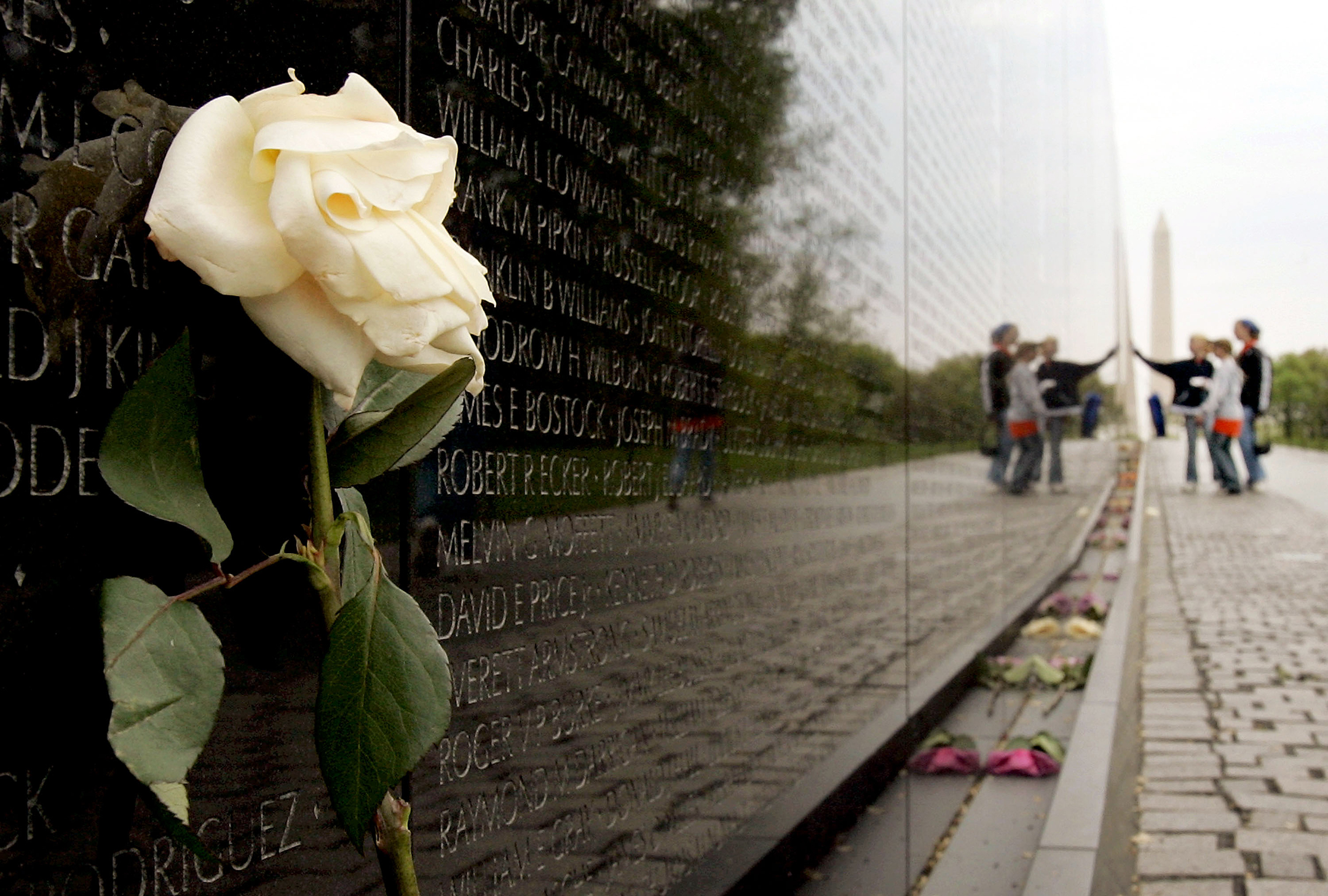 A wide-angle view of the Vietnam Veterans Memorial, with a white flower against the wall in the foreground, a group of students in the background, and the Washington monument behind them