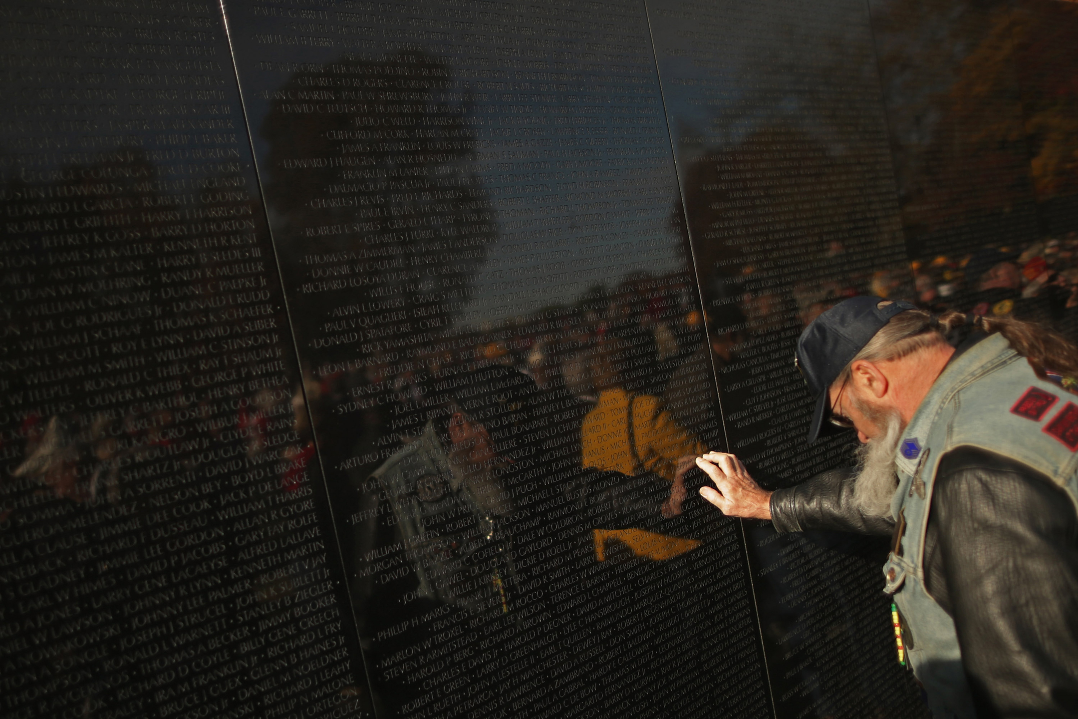 A man with a hat, ponytail, and a vest hangs his head as he touches the Vietnam Veterans Memorial, with his reflection seen in the surface of the monument