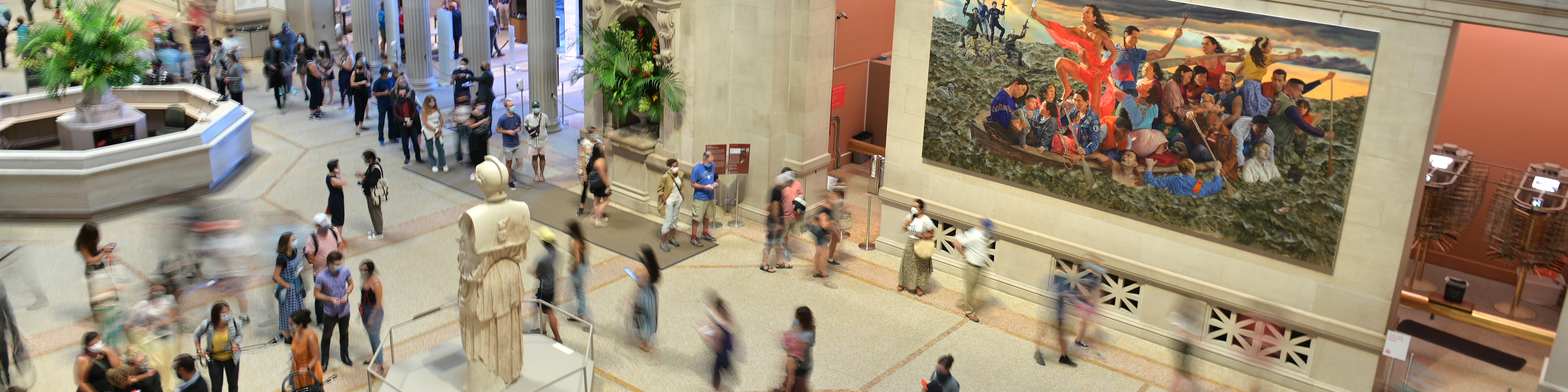 Overhead photograph of people moving around the main lobby of the metropolitan museum of art