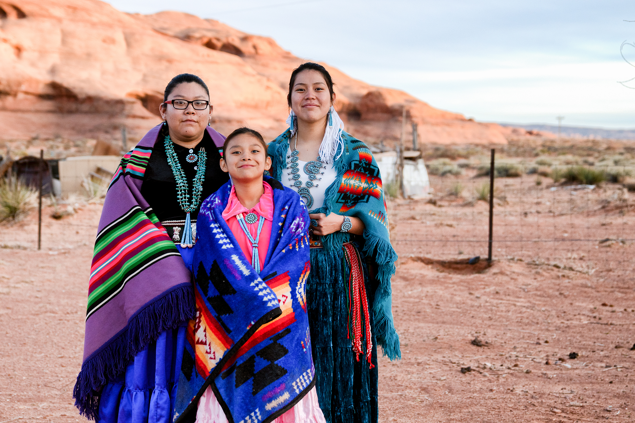 Photo of three young Native American women of various ages, smiling while wearing traditional Navajo dress