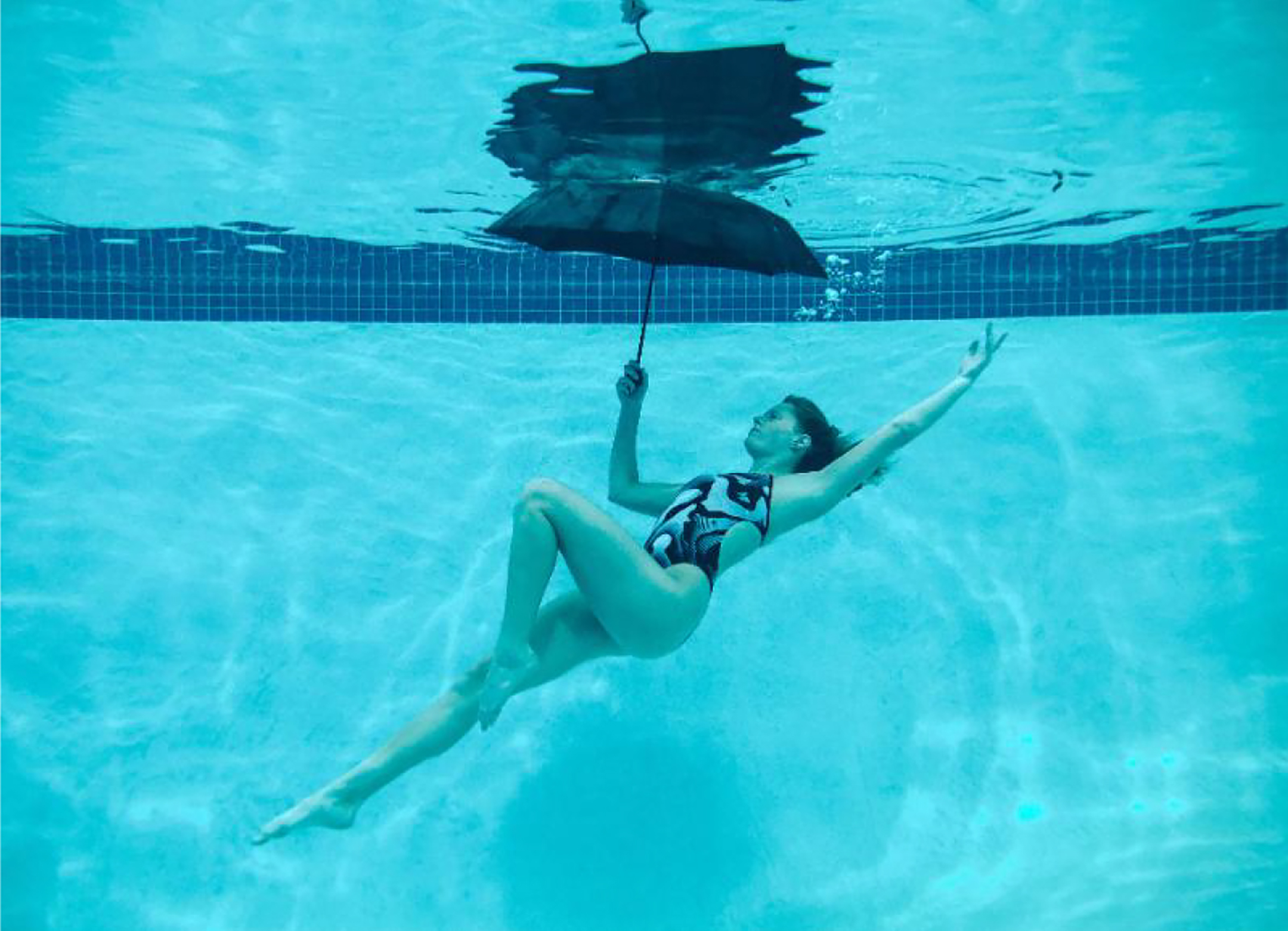 Photograph of a young woman in a swimsuit holding an umbrella while submerged under water in a swimming pool