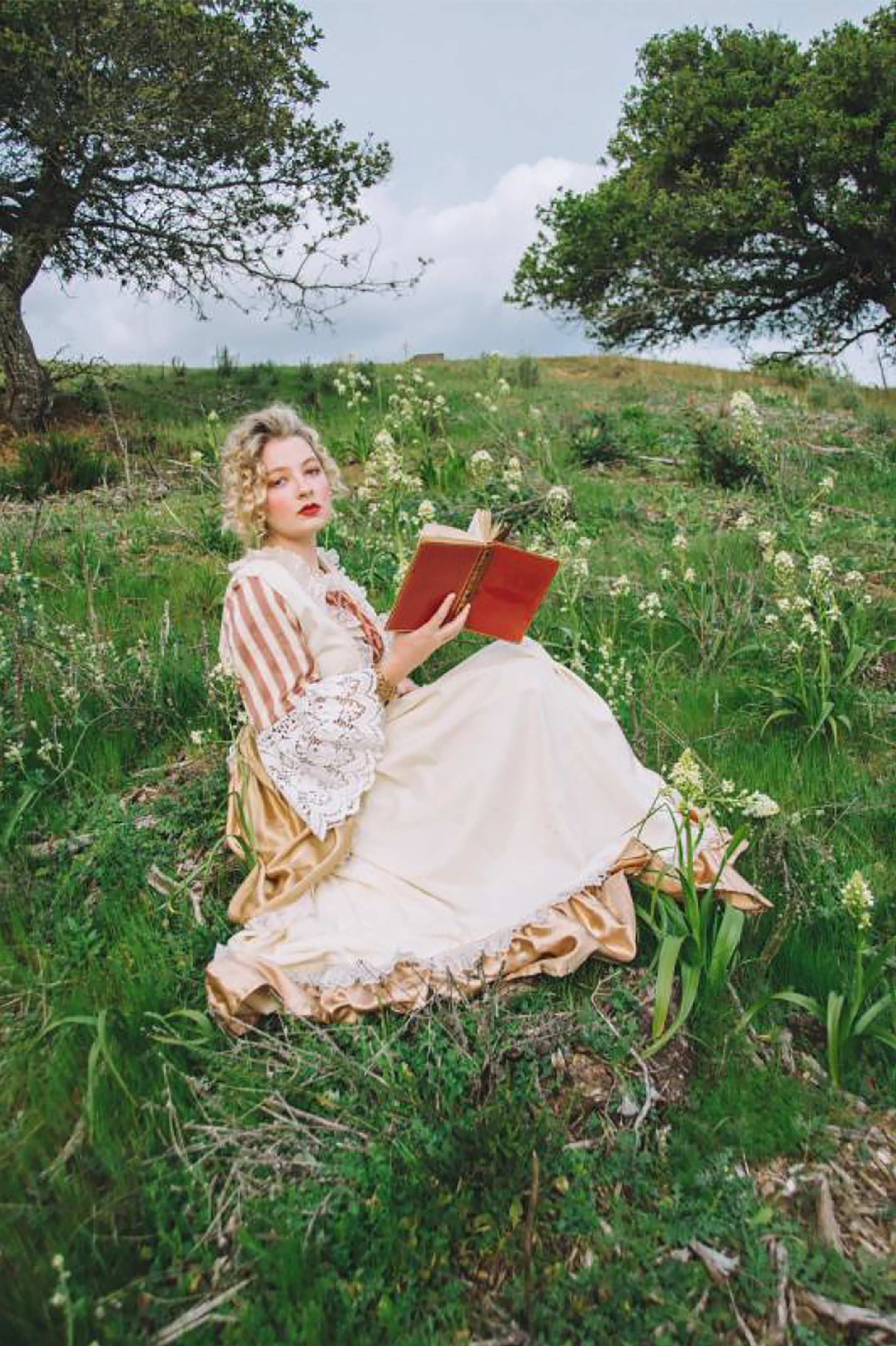 Photograph of a young woman in a victorian dress reclining in a green field while reading a book