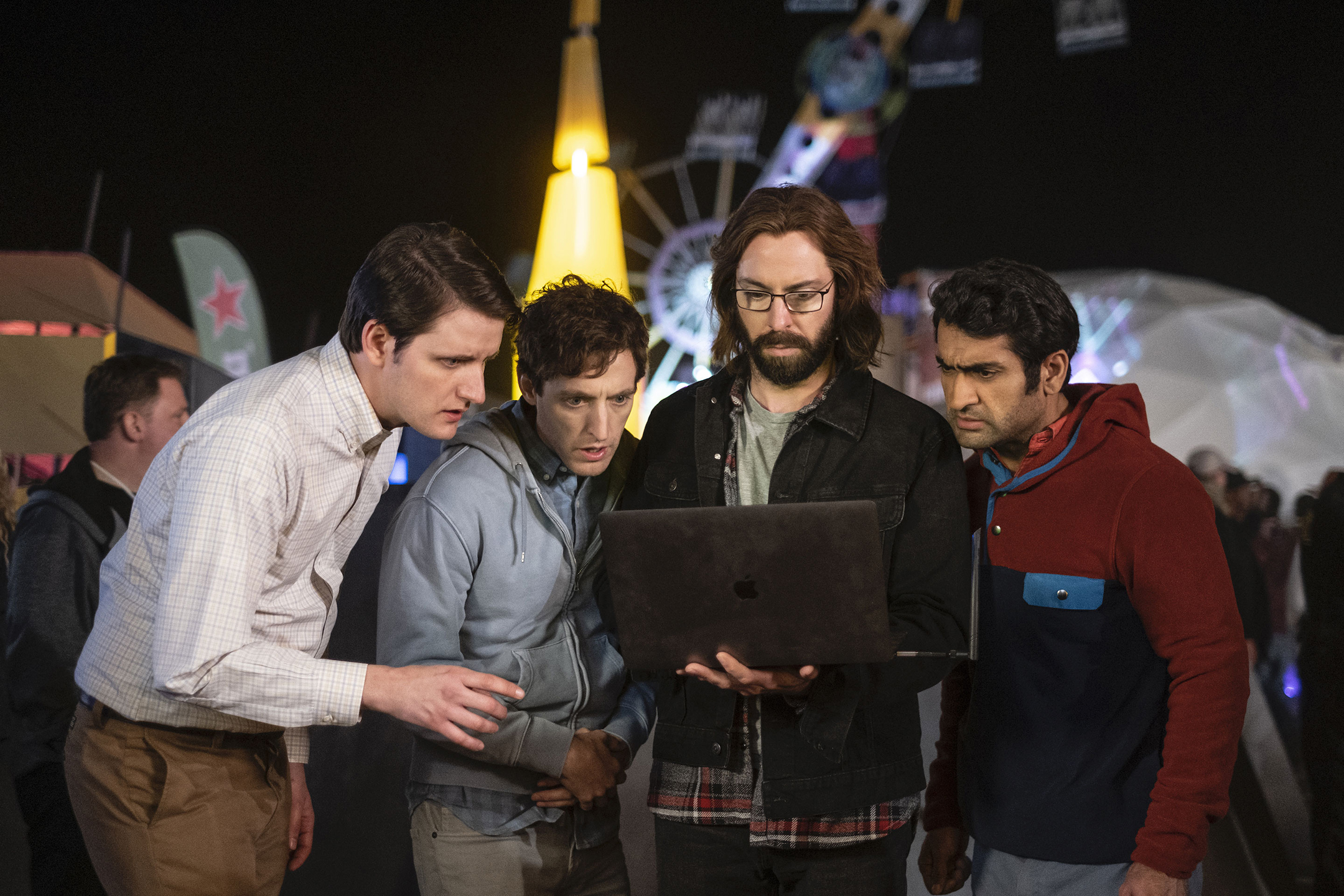 A still from the HBO series Silicon Valley showing four men standing while gaping at an open laptop
