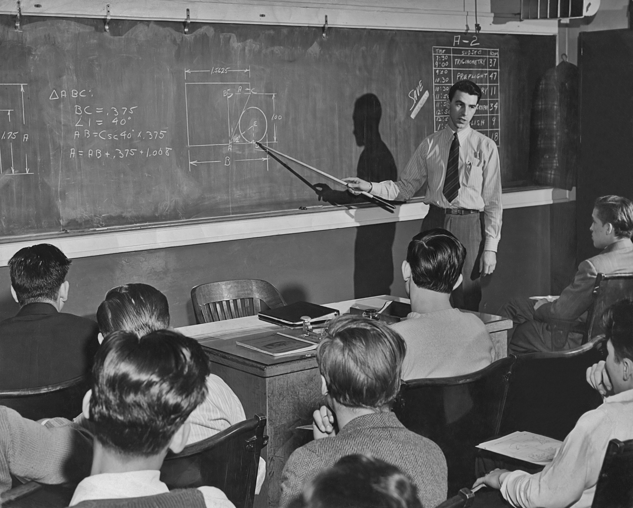 Black and white photo of a male teacher in front of a blackboard pointing at an equation with a stick.
