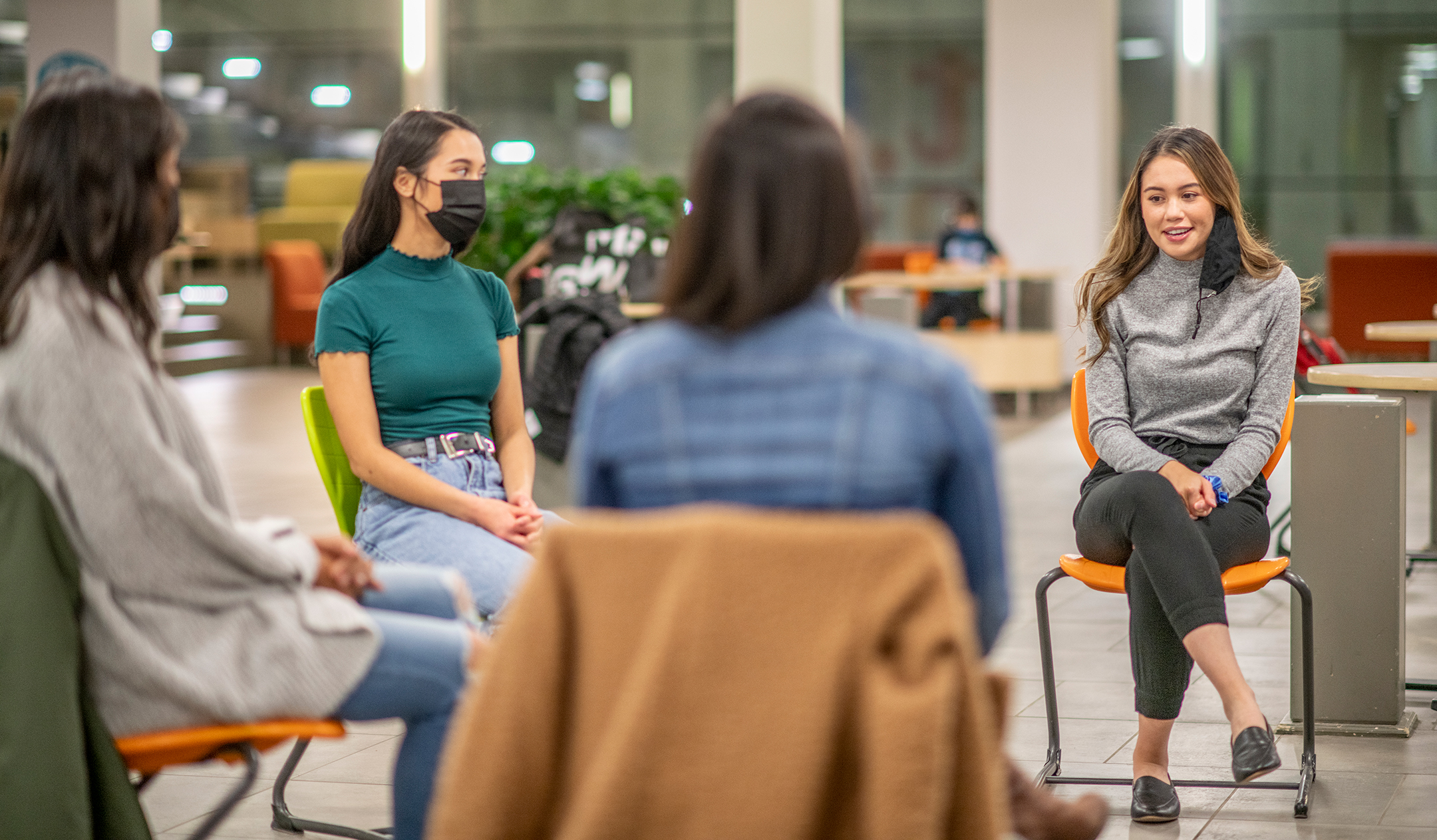 three female students sit in a circle, wearing masks and all socially distanced, listening to a fourth female student as she speaks