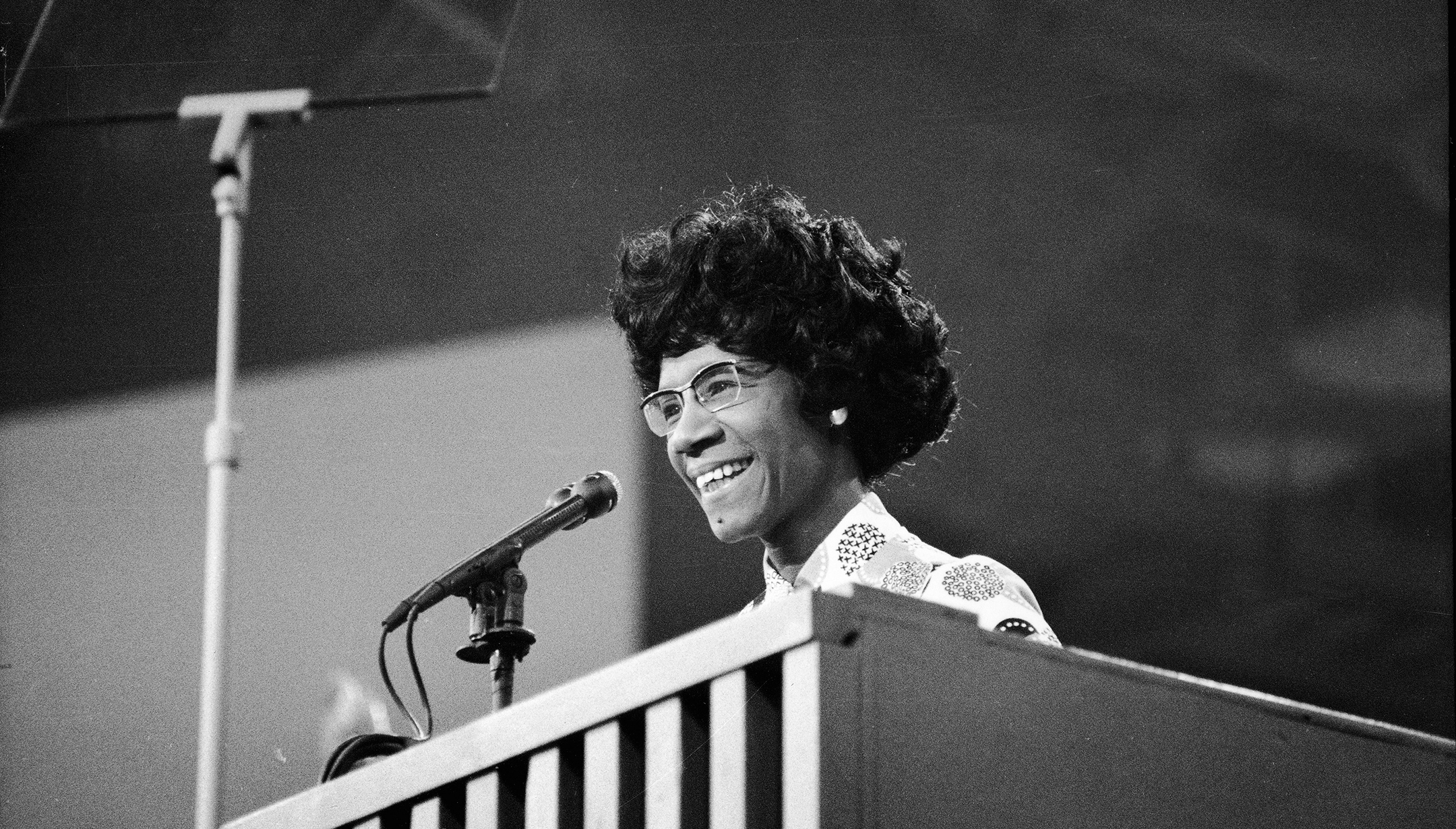 Black and white photo of Shirley Chisholm smiling as she stands at a podium