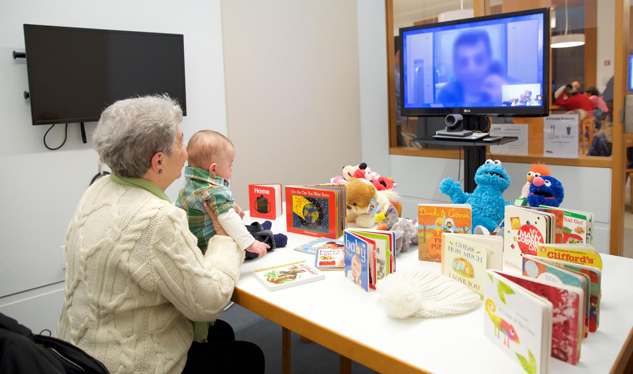 Elderly woman holding a small child sit at a table covered in toys and kids books while connecting with a male loved one, who's face is obscured, via a video screen