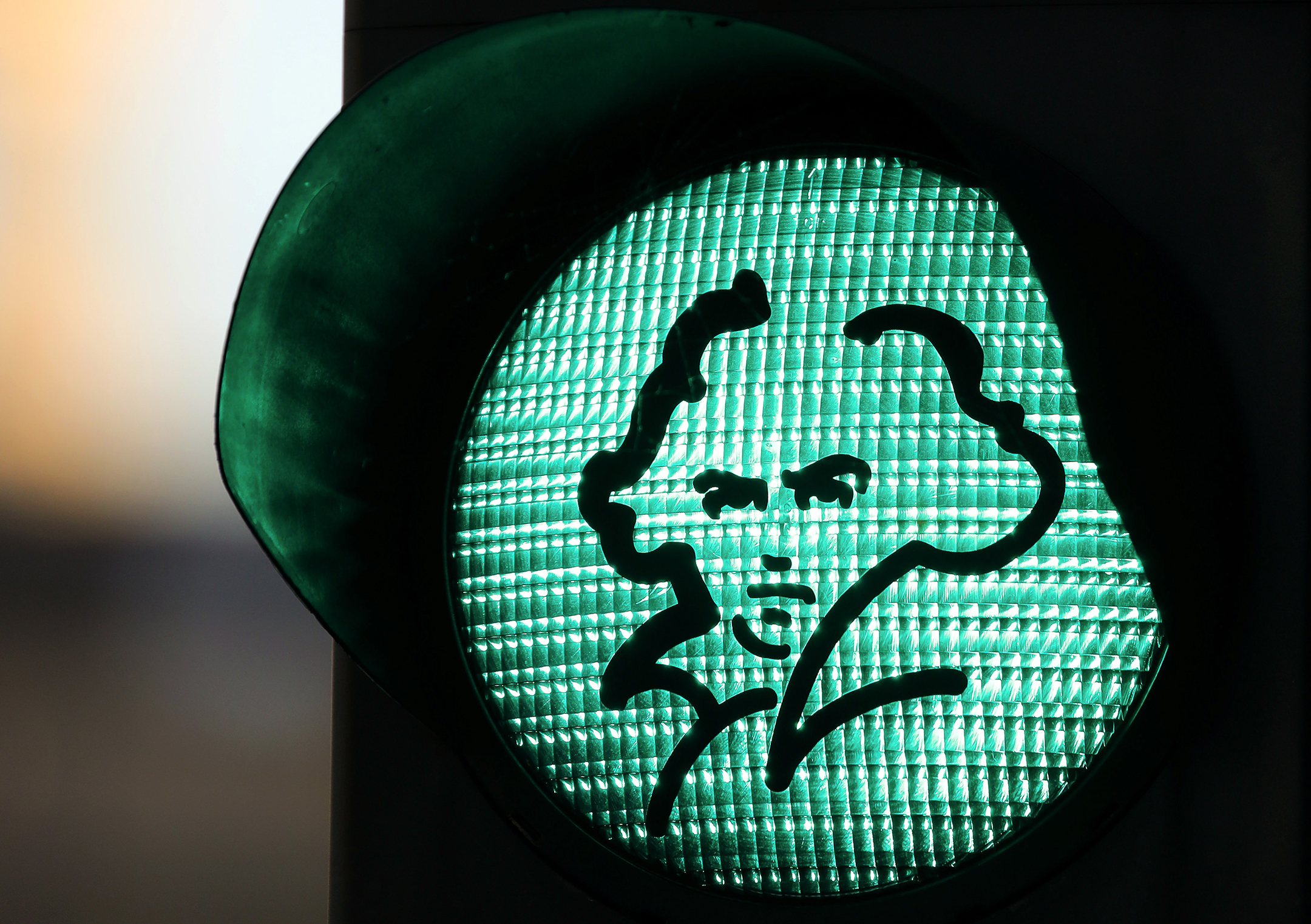 green traffic light with a black outline of beethoven's profile stuck on it