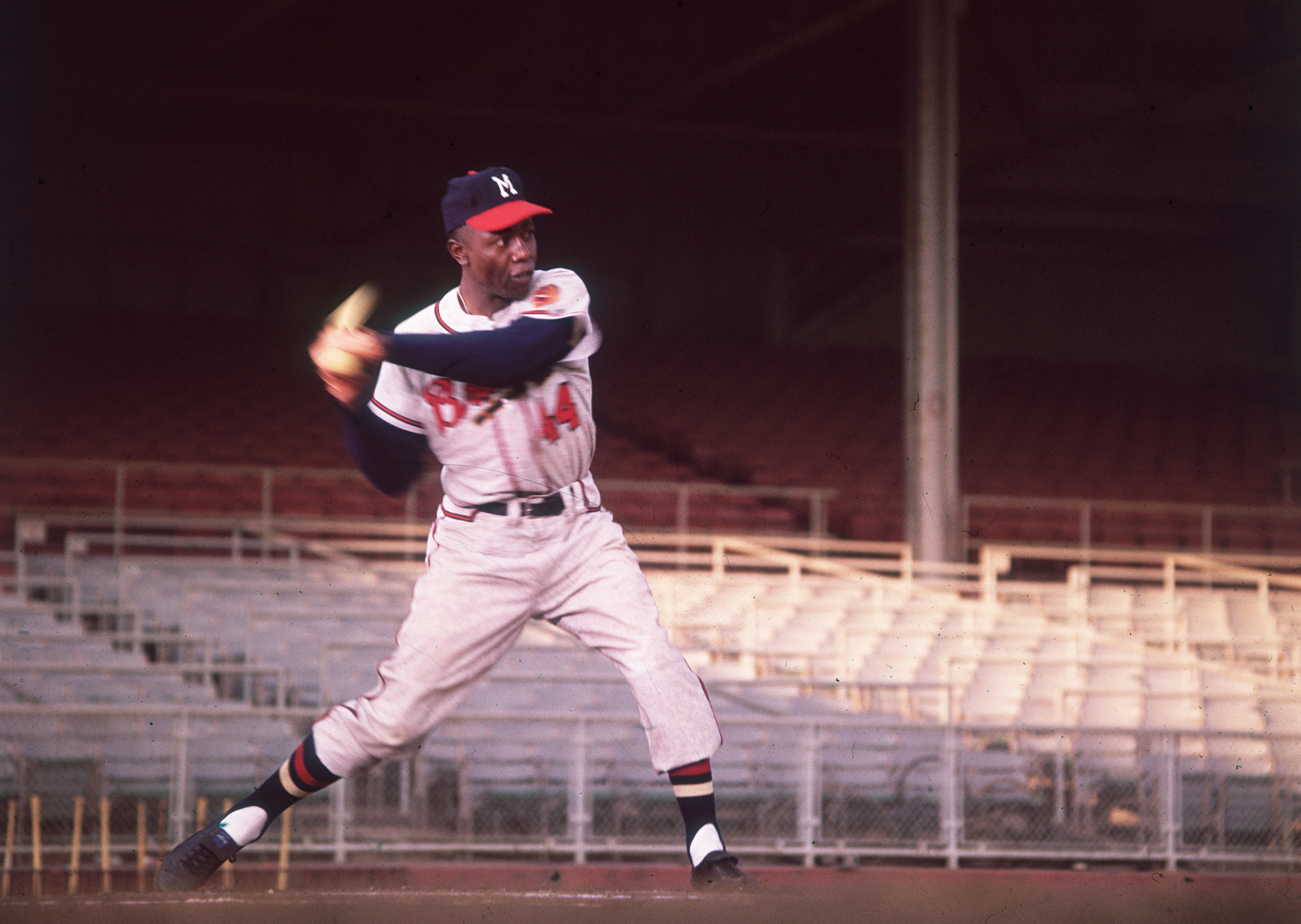 Color photo of professional baseball player Henry Aaron in the middle of swinging his bat in an empty stadium