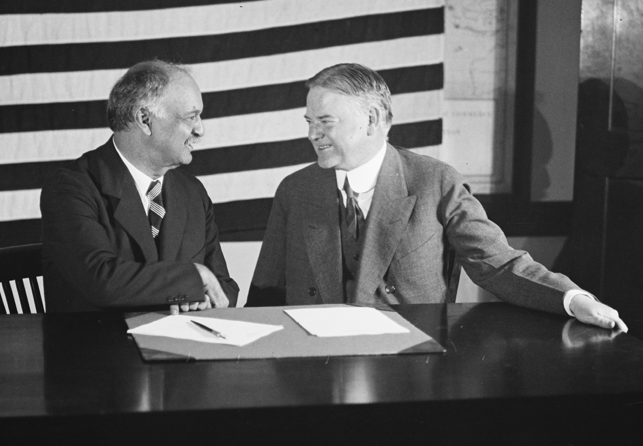 Black and white photo of two men, looking at each other and smiling while sitting at a small desk in front of a large American flag