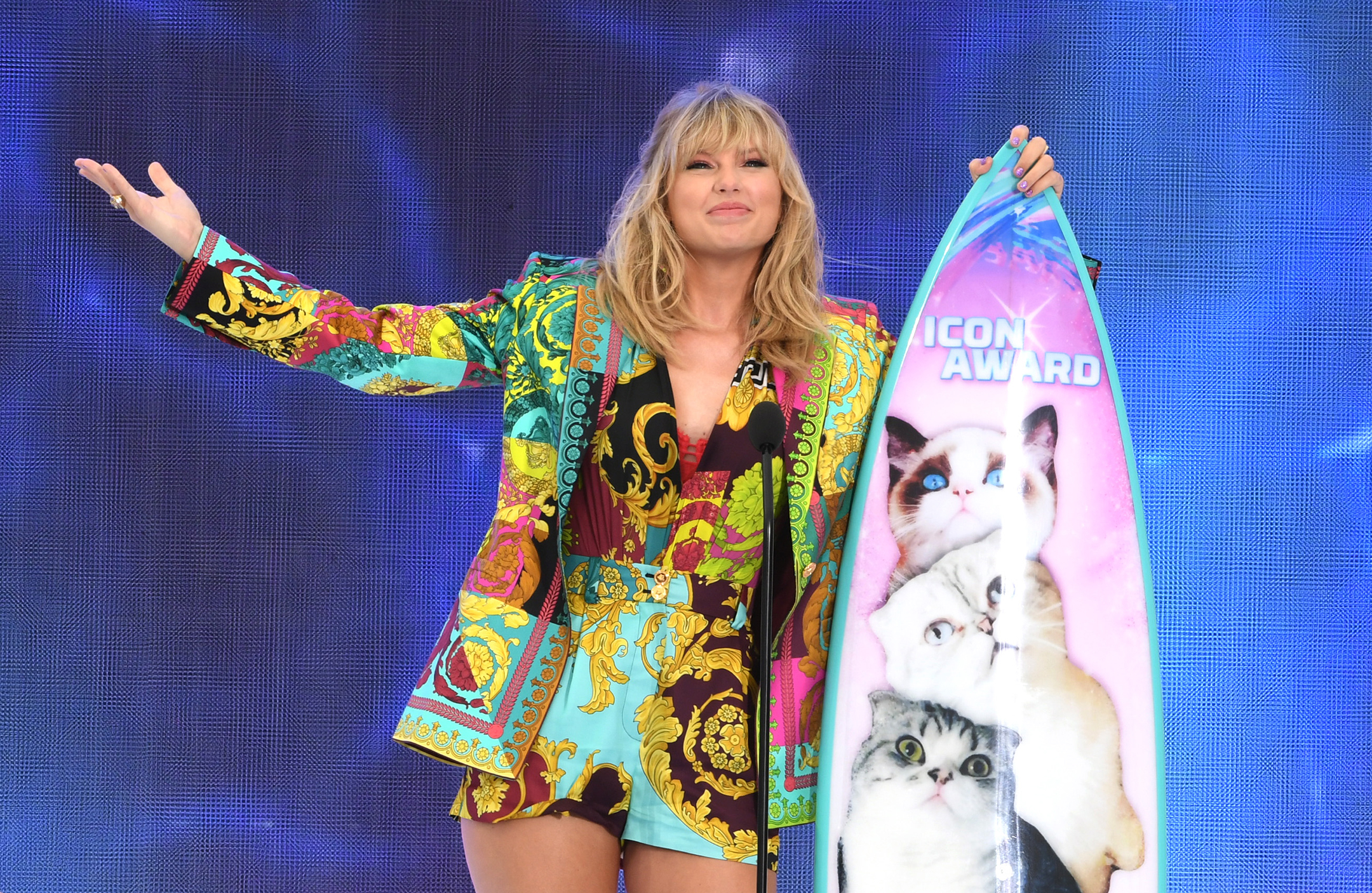 Taylor Swift, wearing a colorful broad-shouldered jacket, smiles as she poses with a surfboard that serves as her trophy for winning the icon award