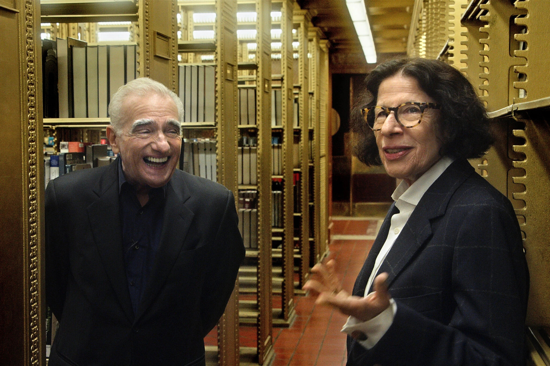 Martin Scorsese, left, laughs while Fran Lebowitz gestures while standing among the stacks of the New York Public Library