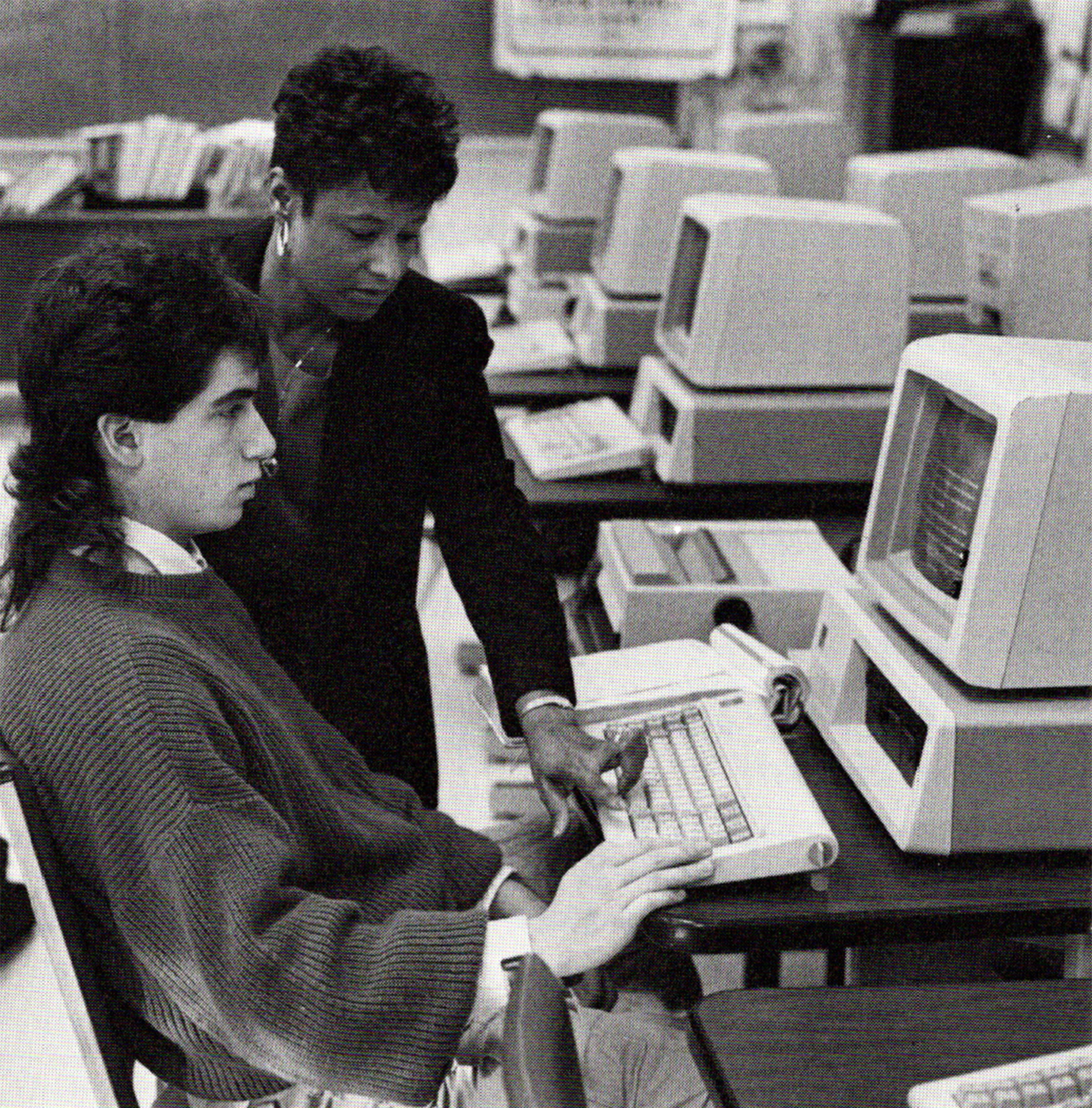 Black and white photo of a black female teacher helping a white male college student who is sitting at a computer