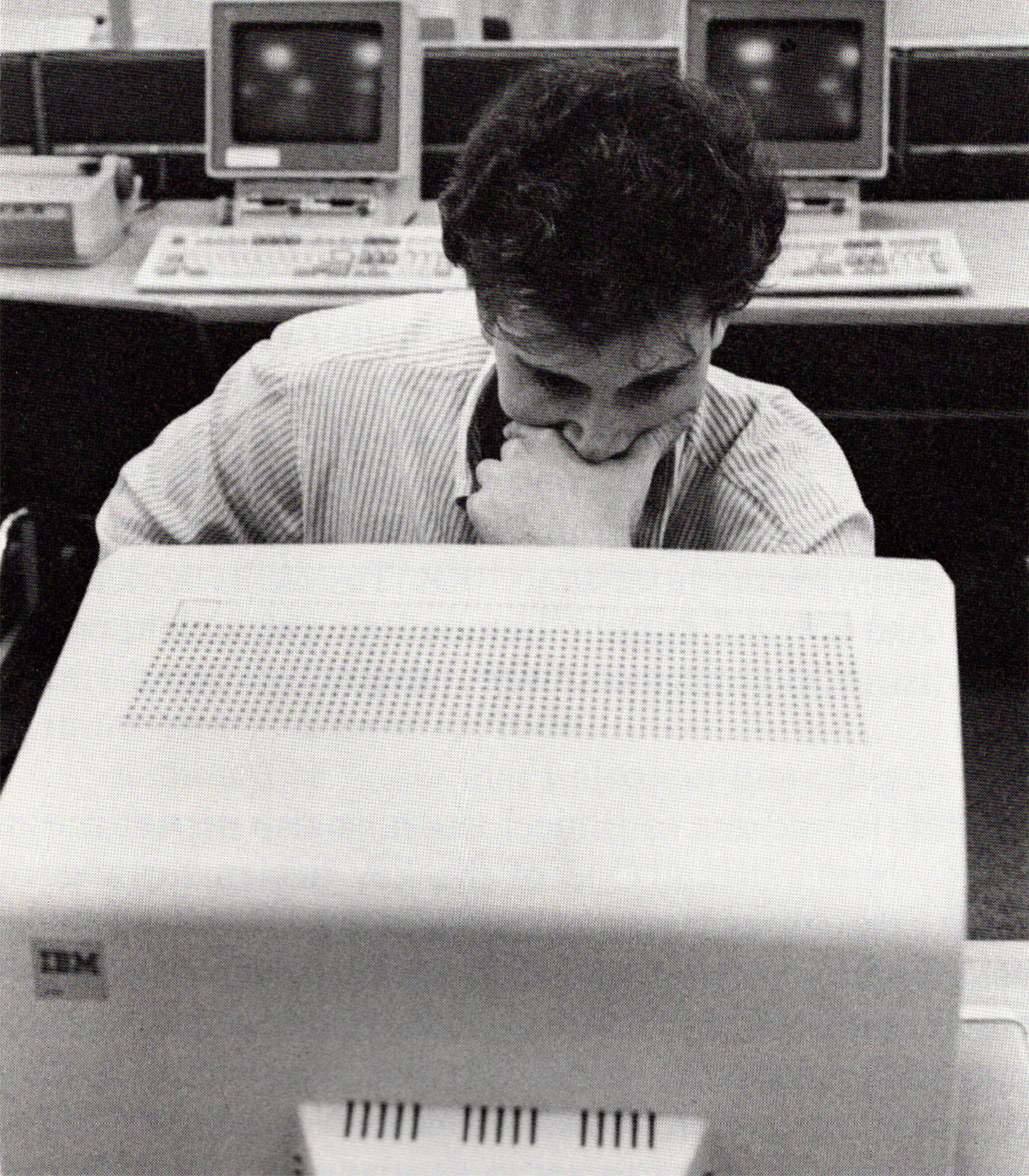Black and white photo of a male college student with his hand against his mouth and chin, looking pensively at a computer screen